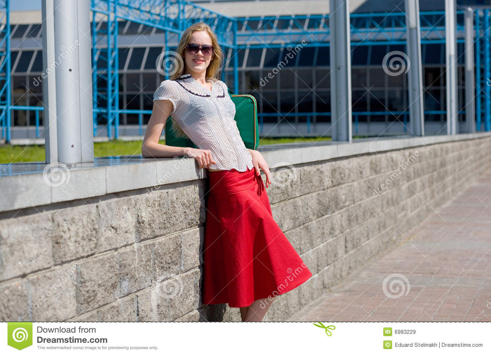 Muchacha rubia atractiva sonriente que desgasta la falda roja