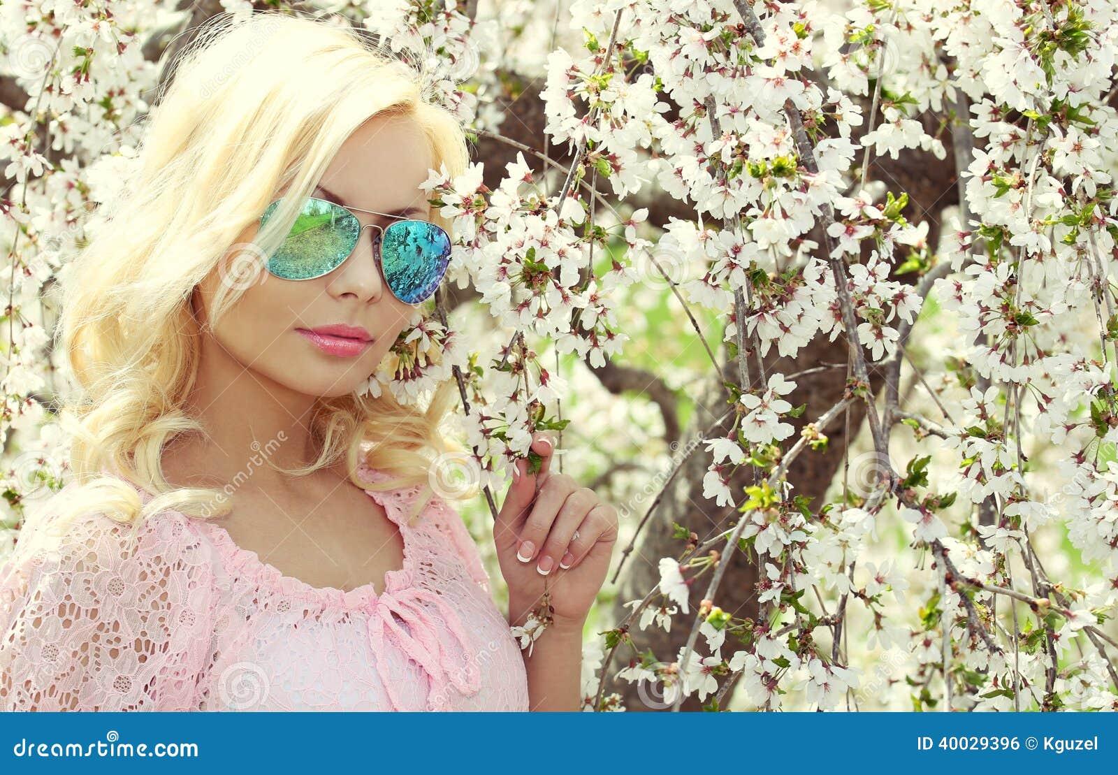 Muchacha rubia con el aviador Sunglasses sobre Cherry Blossom. Primavera