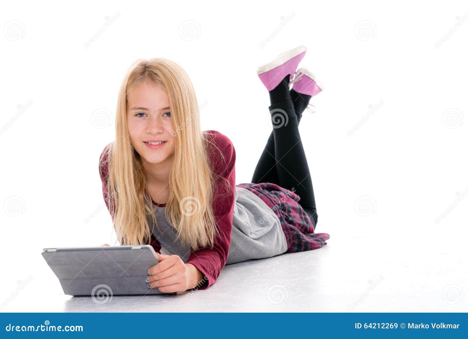 Muchacha rubia con la PC de la tableta que miente en el piso