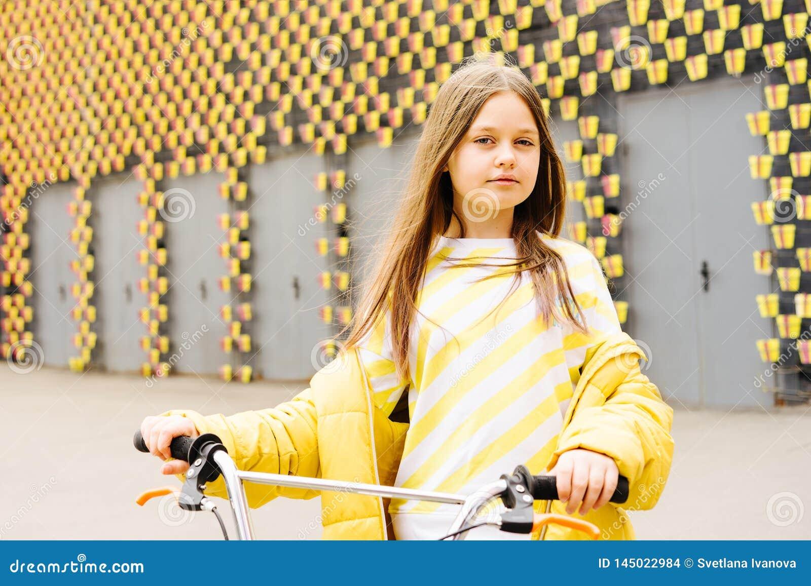 Muchacha rubia de pelo largo en un suéter amarillo y una chaqueta amarilla