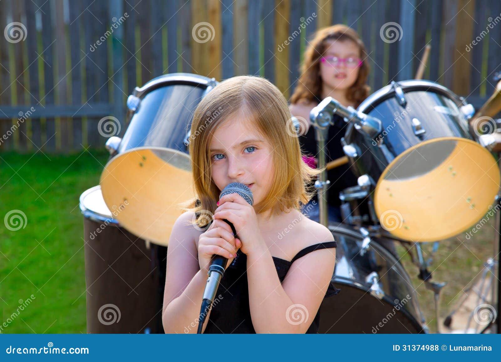 Muchacha rubia del niño que canta en patio trasero del tha con los tambores