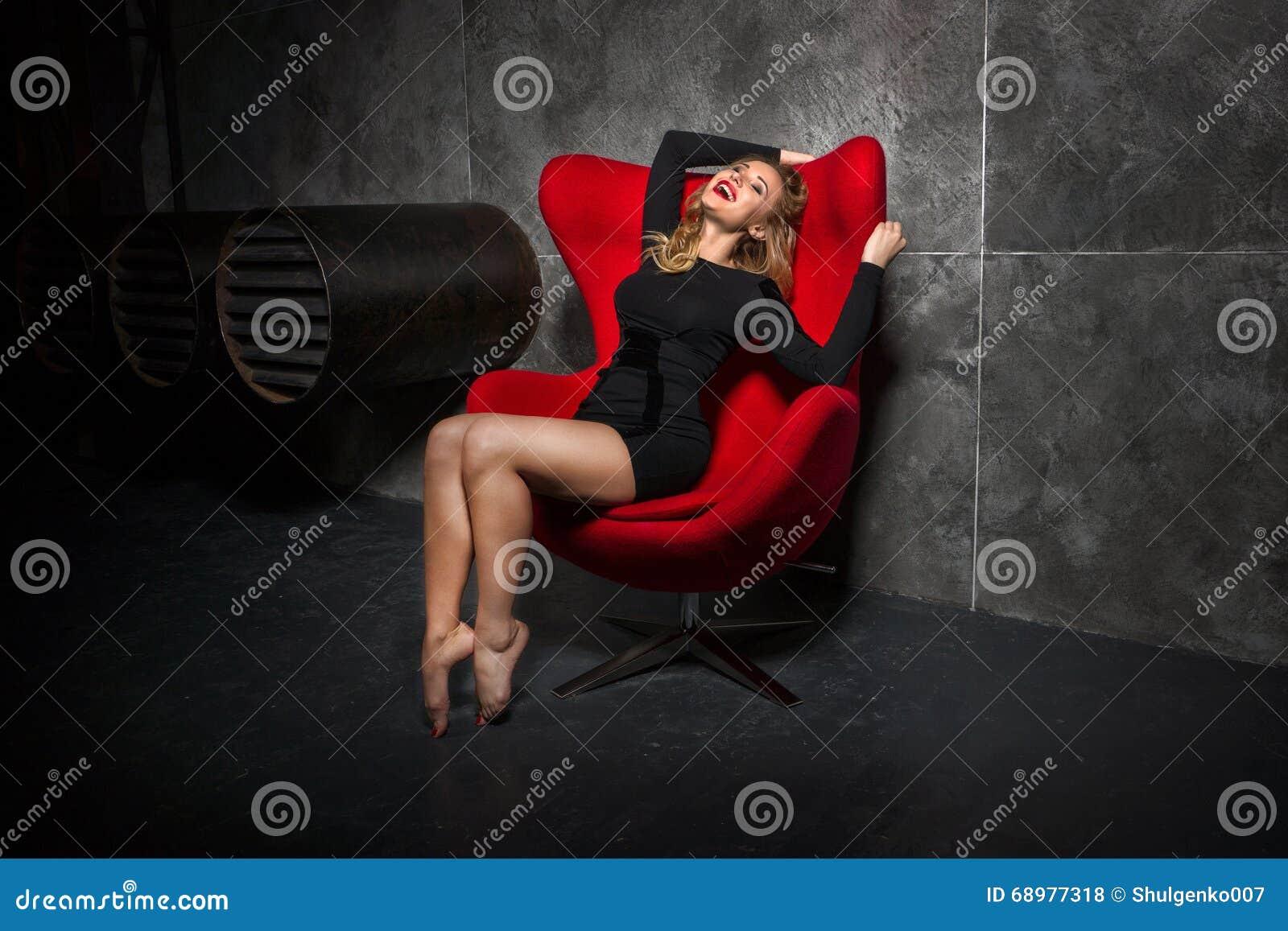 Muchacha rubia en el vestido negro que se sienta en la butaca roja