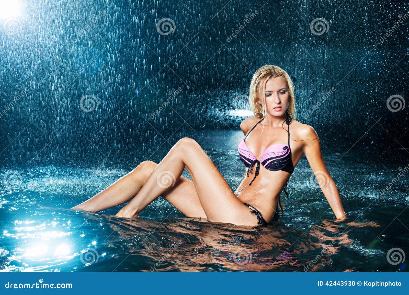 Muchacha rubia en un bañador en el agua