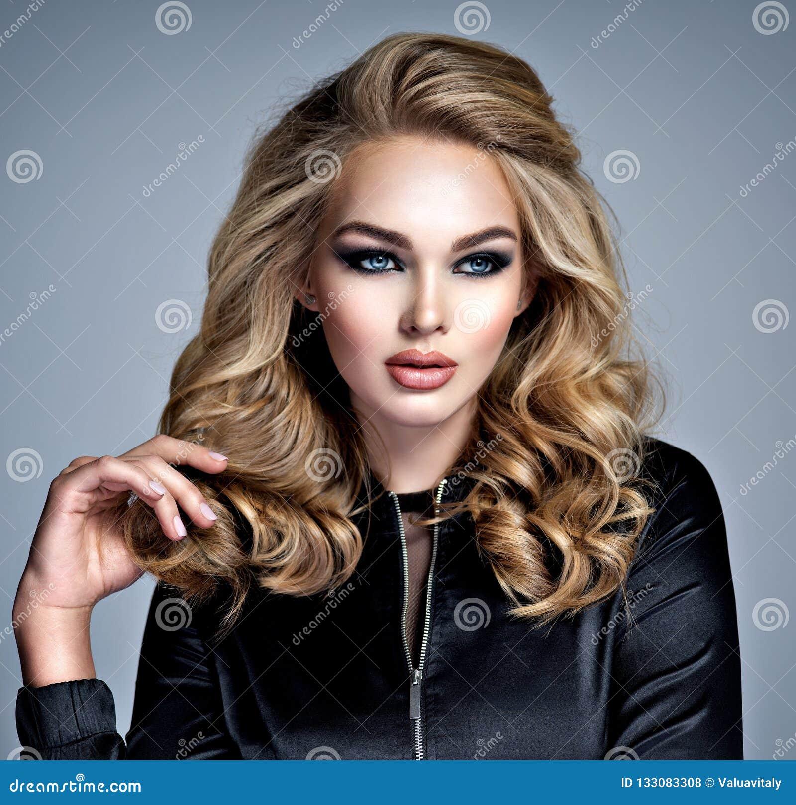 Muchacha rubia hermosa con maquillaje en ojos ahumados del estilo