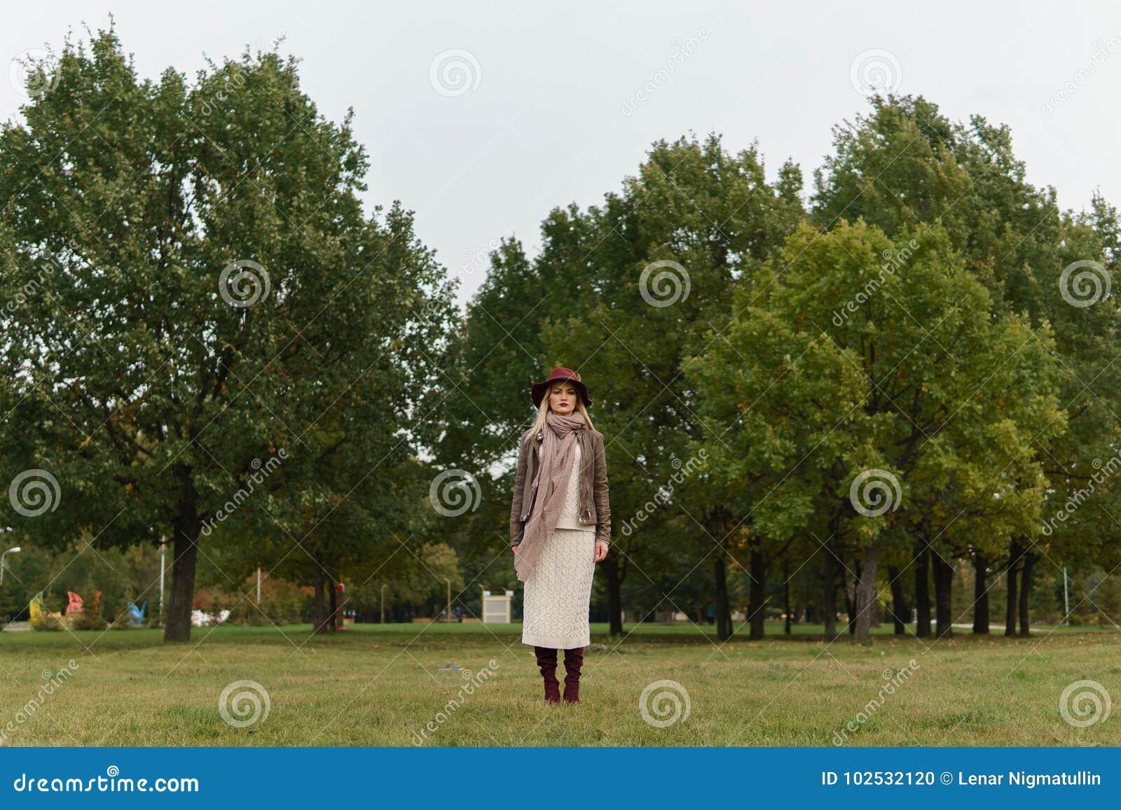 Muchacha rubia hermosa que camina en el parque