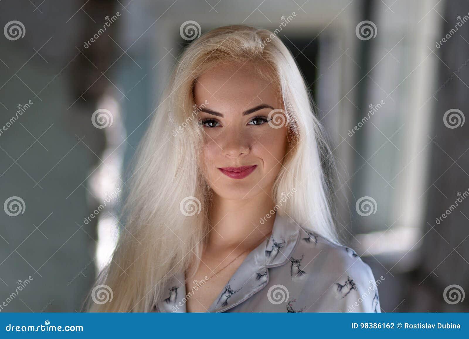 Muchacha rubia joven hermosa con una cara bonita y sonrisa hermosa de los ojos El retrato de una mujer con el pelo largo y sorpre