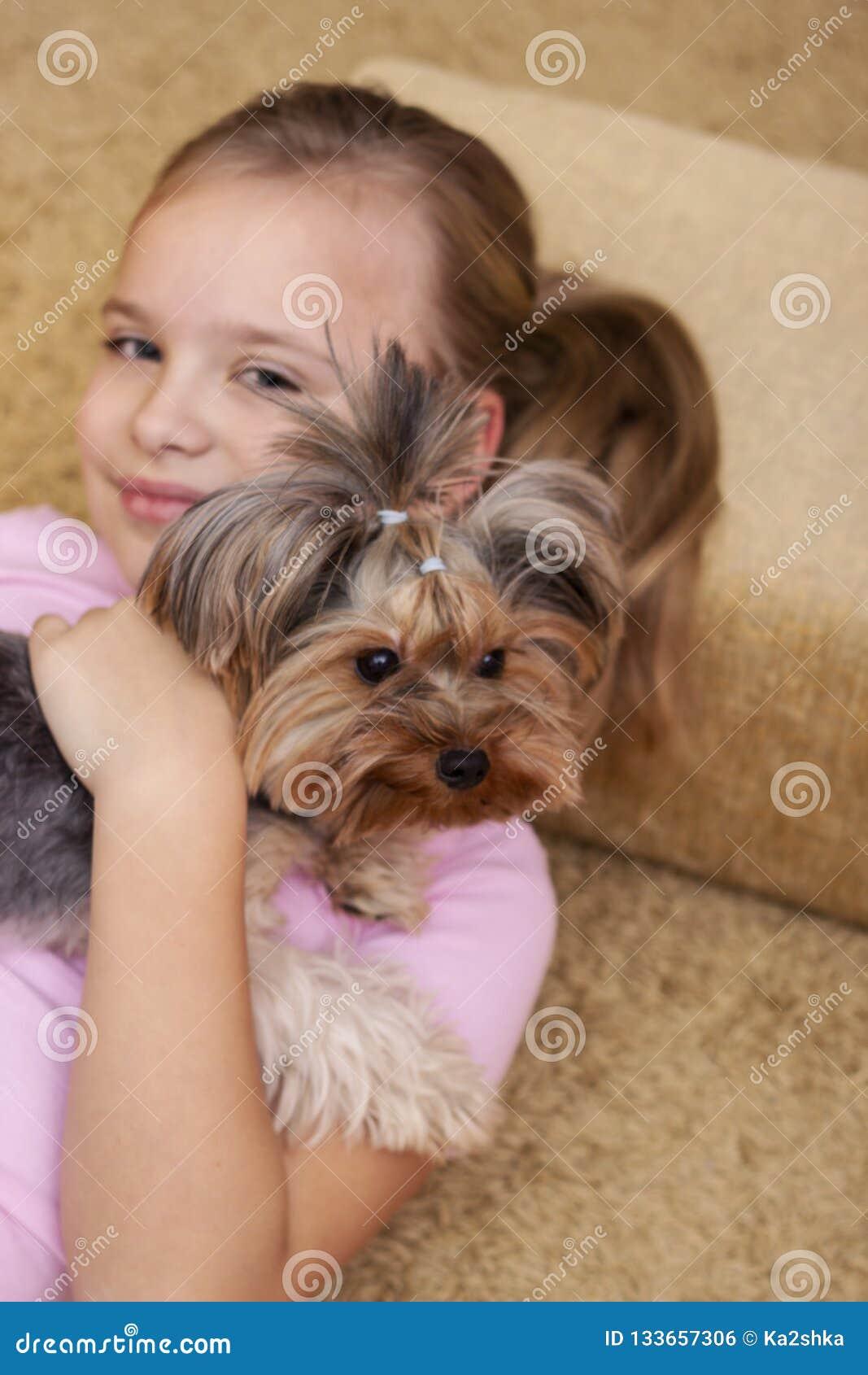 Muchacha rubia joven linda con su perrito del terrier de Yorkshire que miente en el sofá