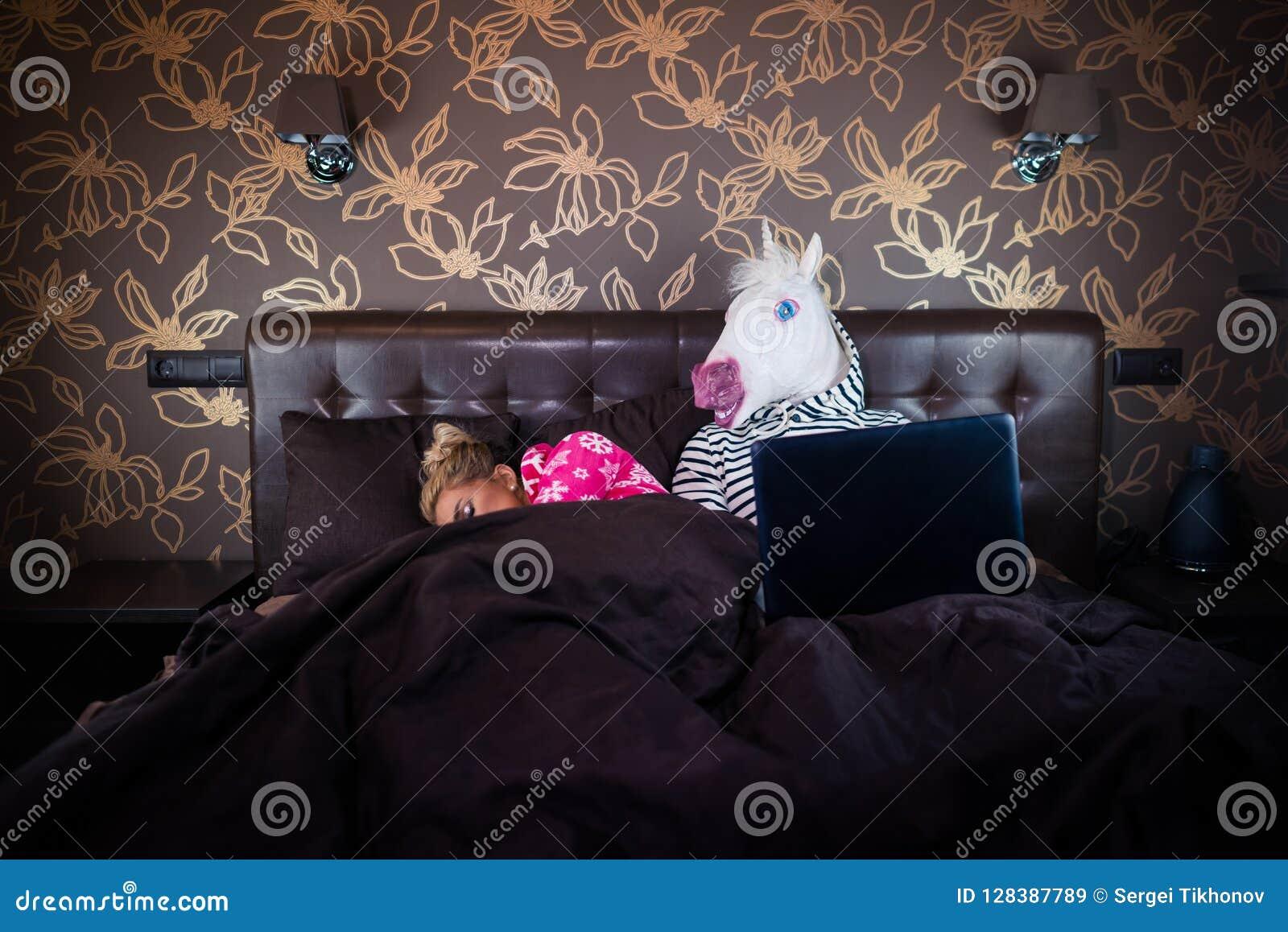 Muchacha rubia que duerme con el hombre divertido en máscara cómica Pares inusuales