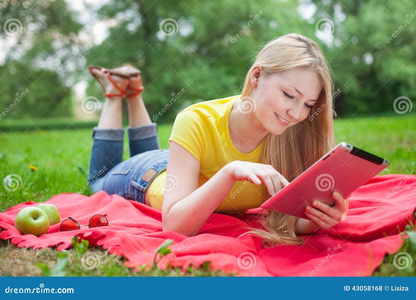 Muchacha rubia que miente en el parque con la tableta en la sobrecama roja