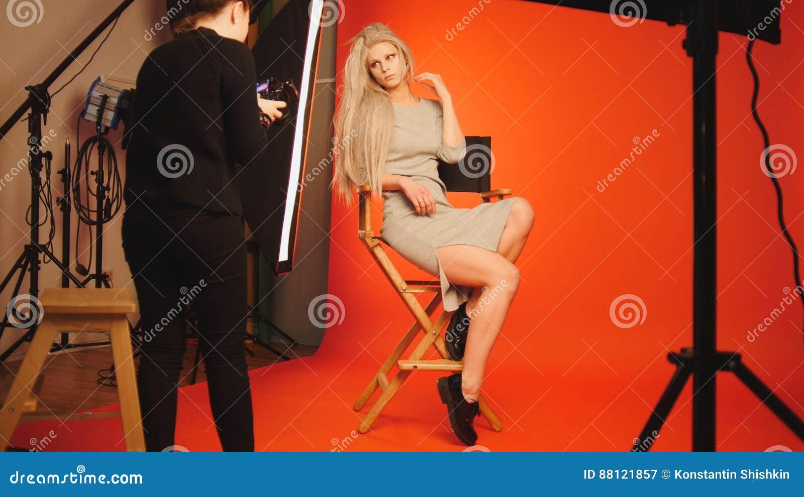 817ed3737e Muchacha rubia que presenta en el estudio para el fotógrafo - fondo del  blanco de la sesión de foto. Imágenes stock más similares
