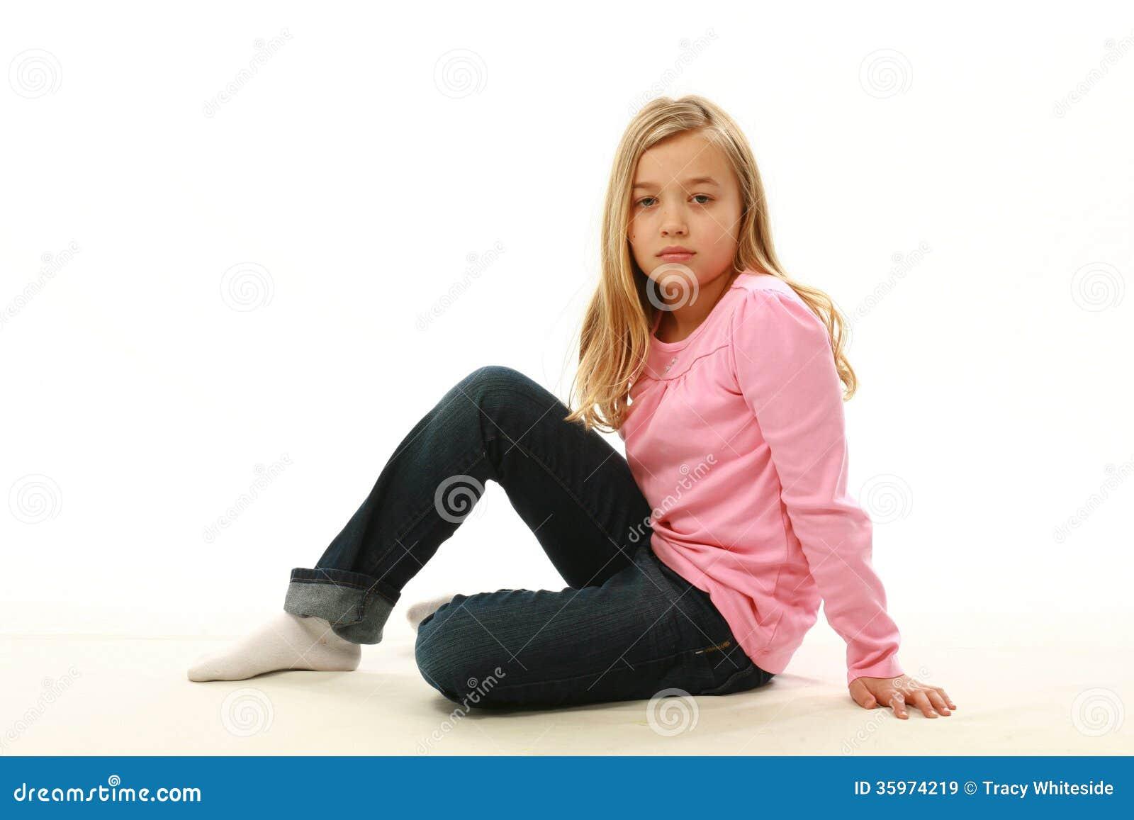 Muchacha rubia que se sienta en piso