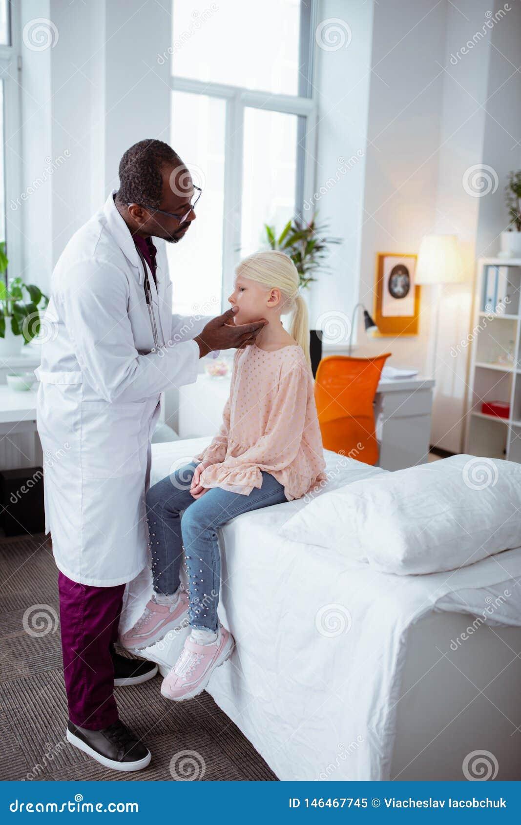 Muchacha Rubio-cabelluda que tiene un poco de garganta dolorida que viene al doctor