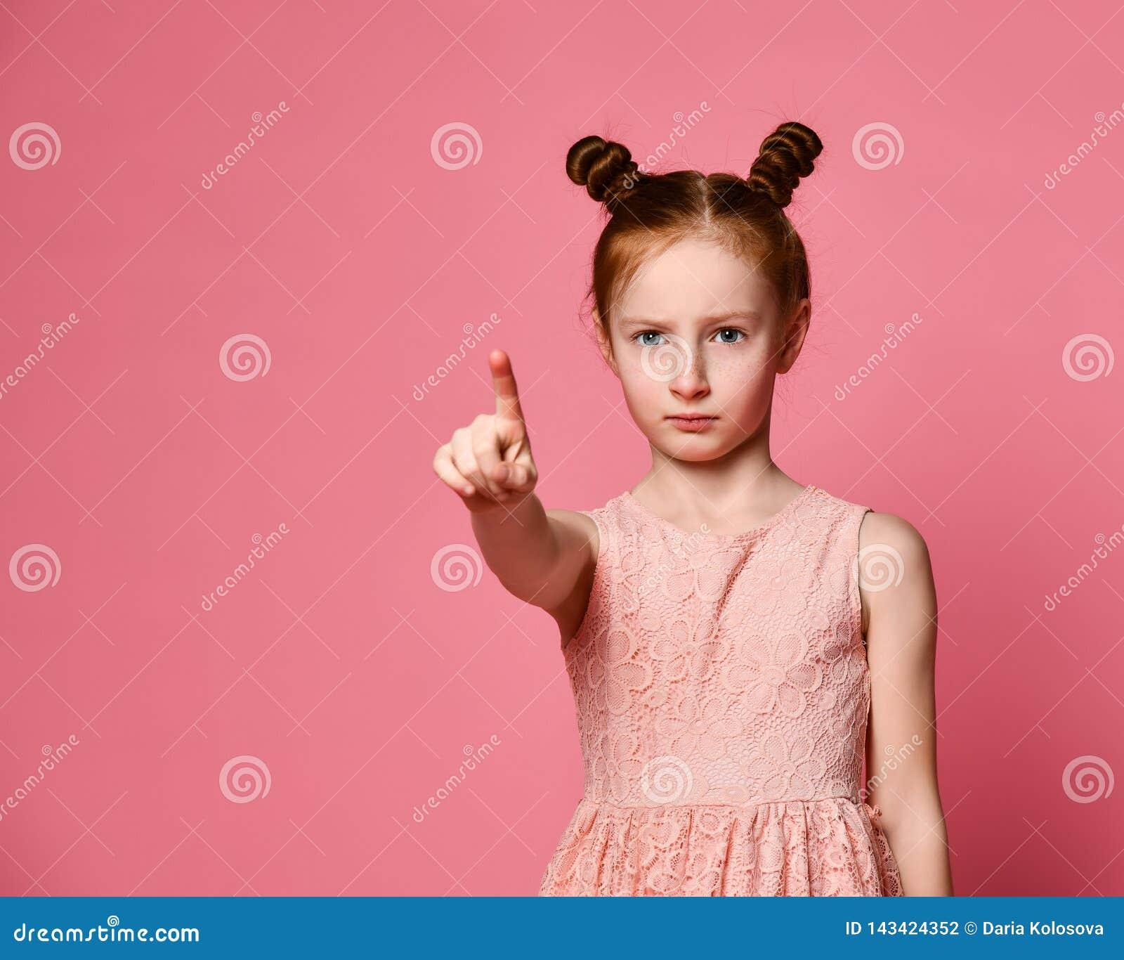 Muchacha seria del pelirrojo sobre la pared rosada que señala con confianza en usted con un finger