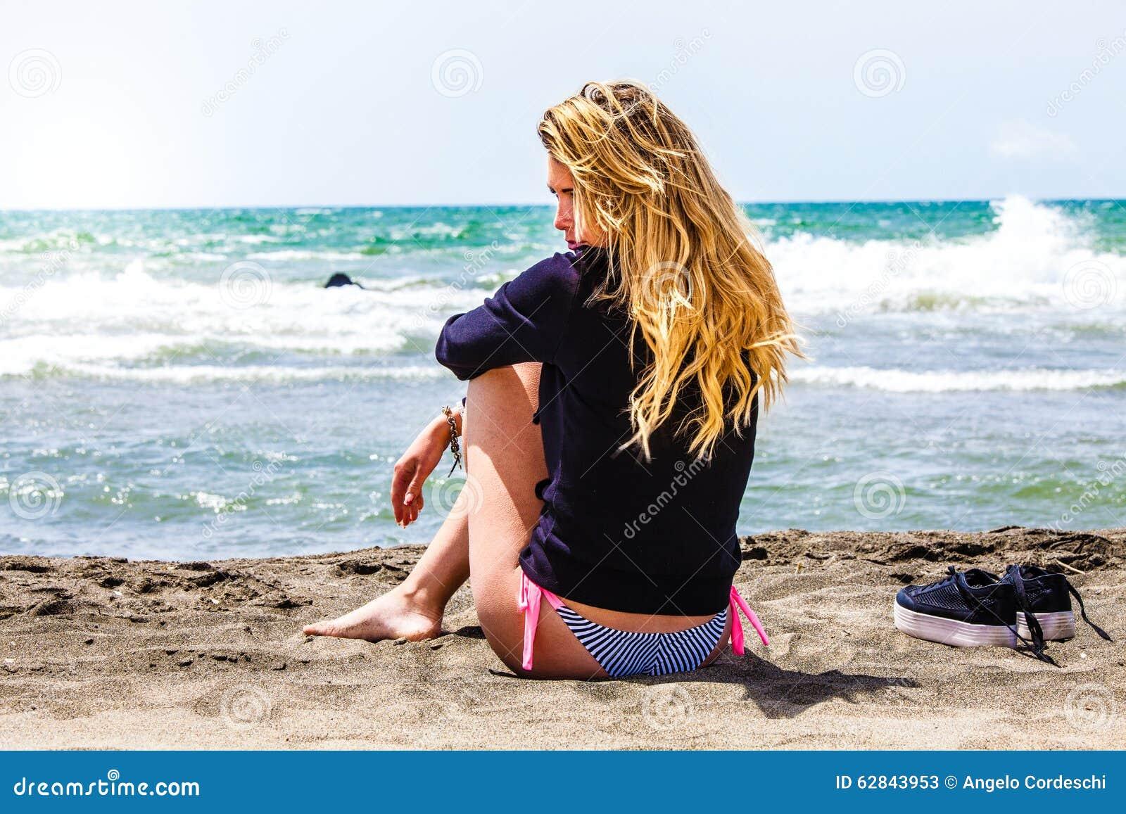Muchacha sola que se sienta en la playa con el mar Pensativo y cariñoso Decepción en amor
