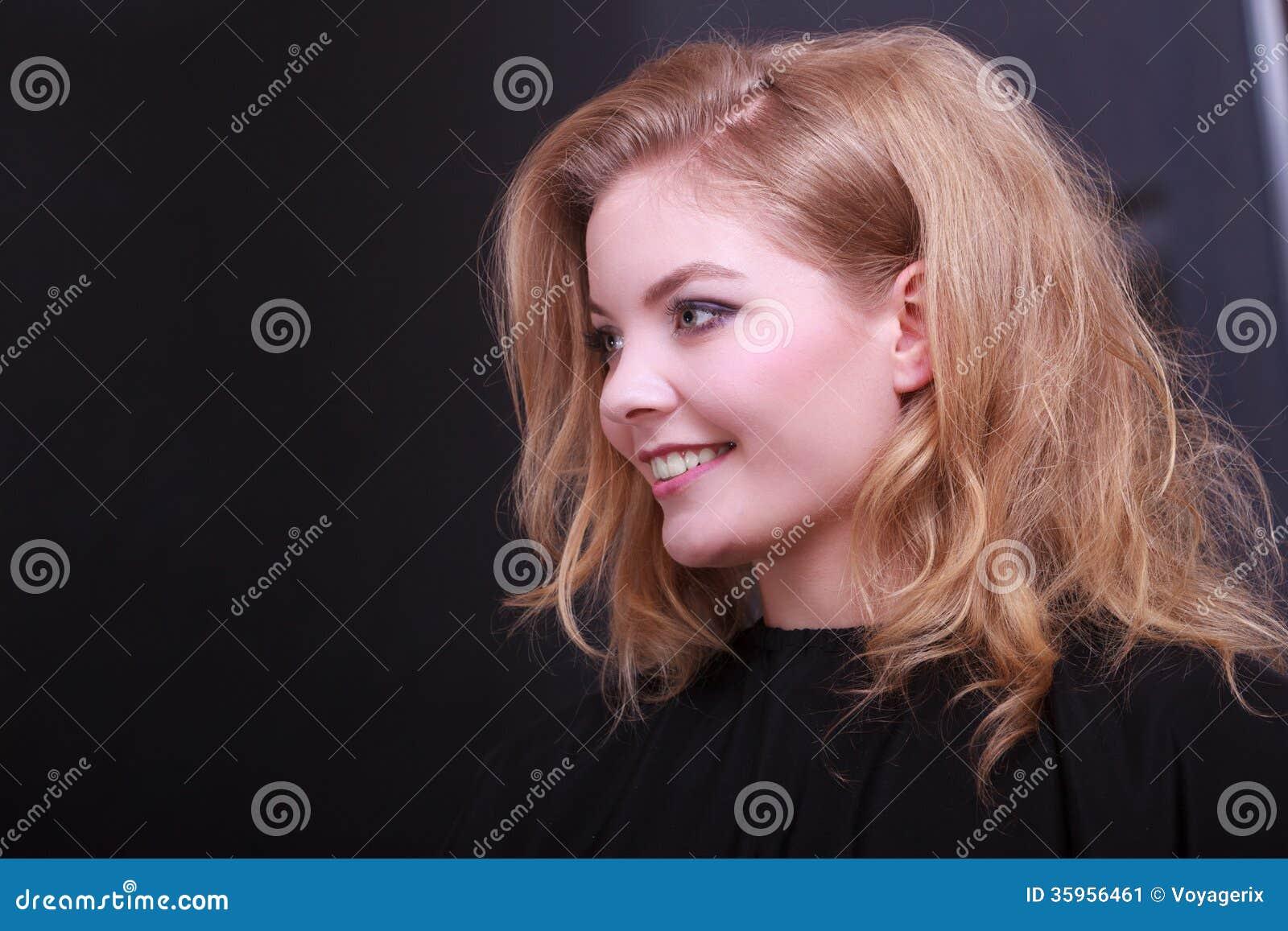 Muchacha sonriente con el pelo ondulado rubio del peluquero en salón de belleza