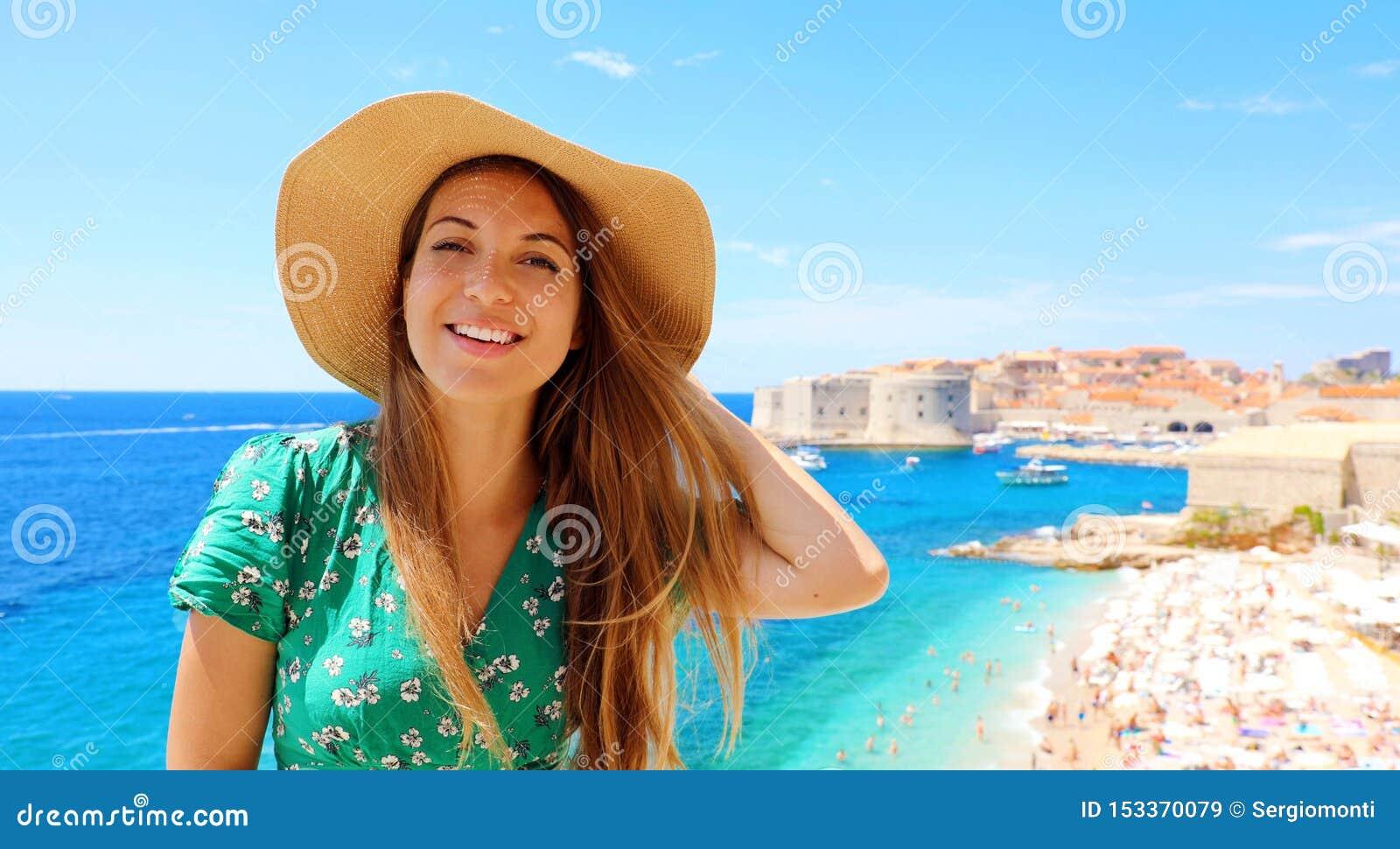 Muchacha sonriente del viajero con el sombrero en Croacia Mujer joven feliz que visita la ciudad vieja de Dubrovnik en el mar Med