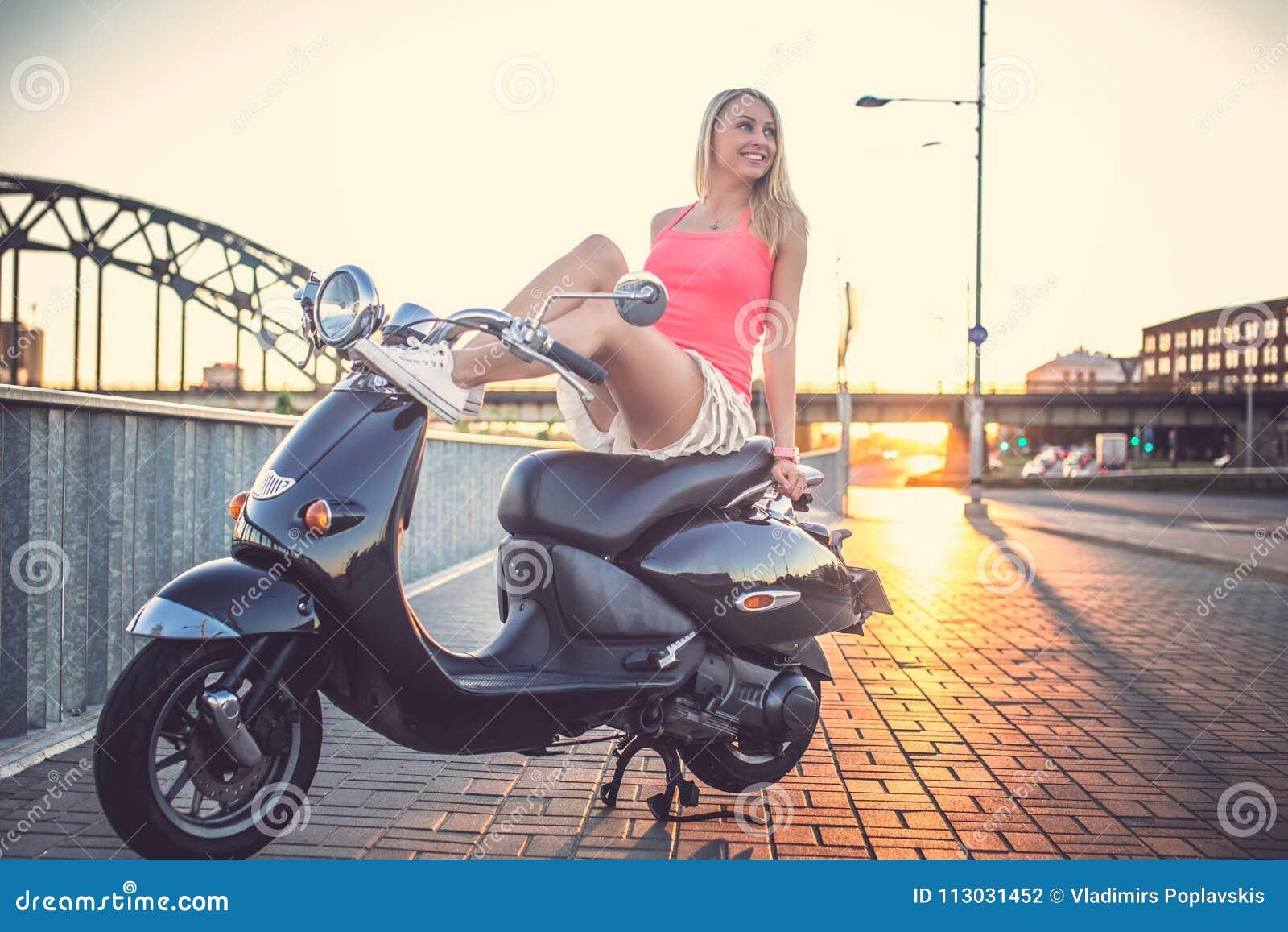 Muchacha sonriente en la vespa del moto