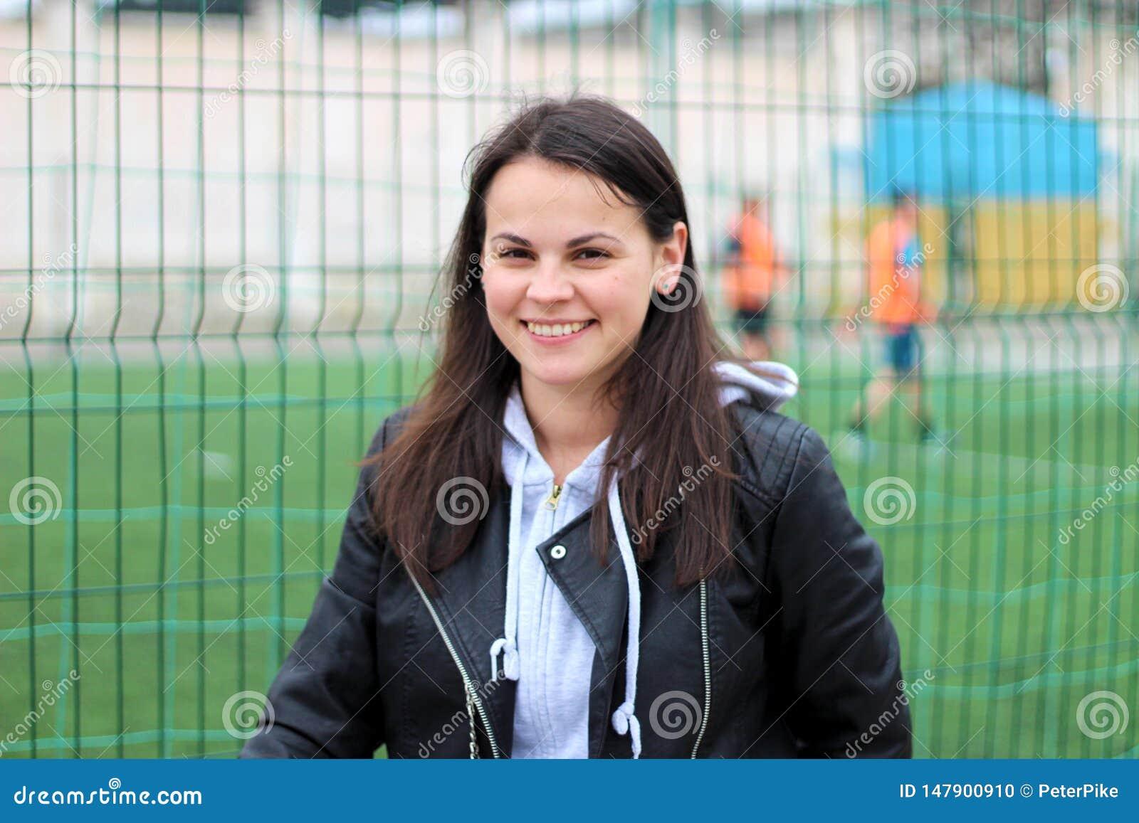 Muchacha sonriente en una chaqueta de cuero y sudadera con capucha contra la perspectiva de jugar a futbolistas