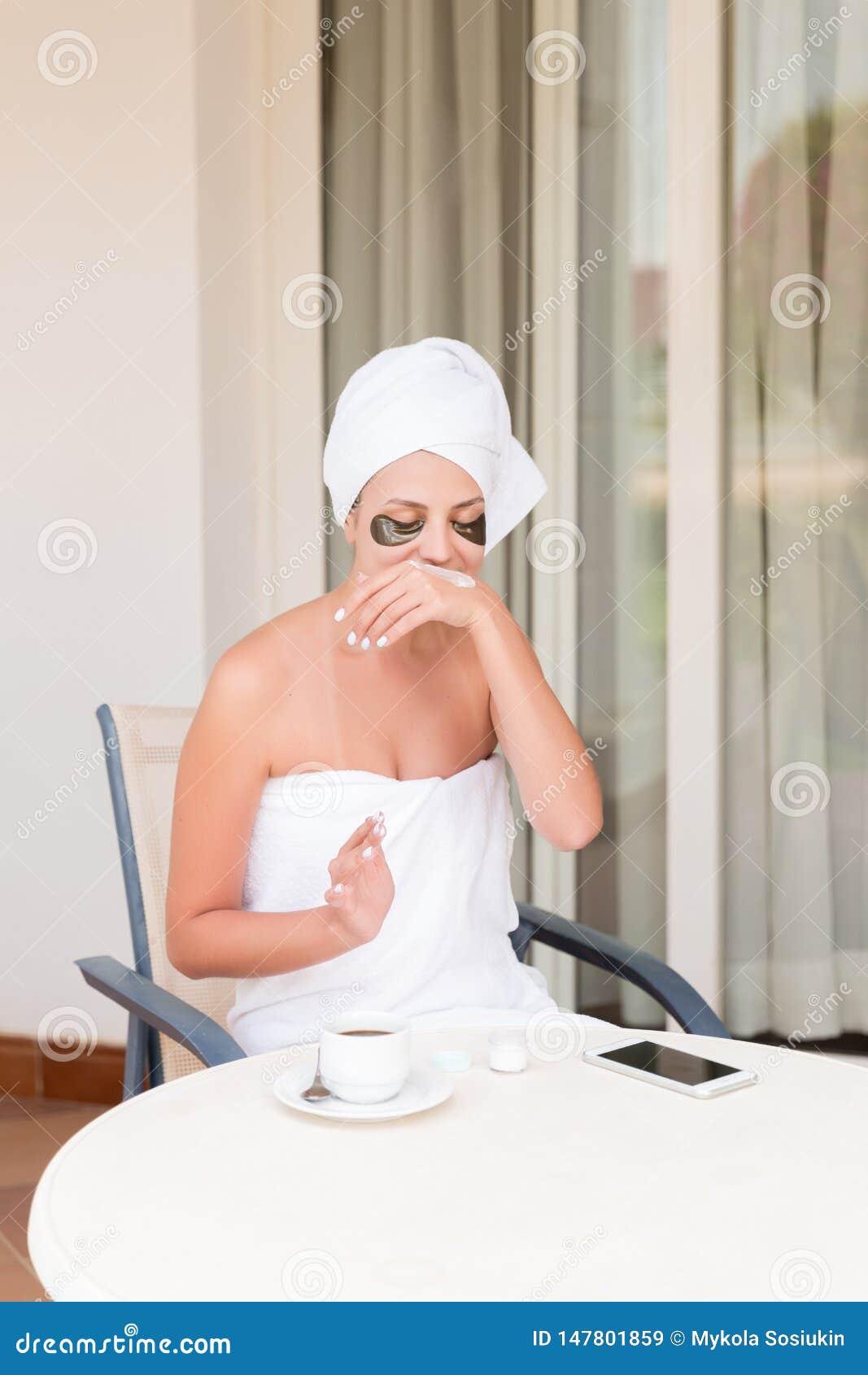 Muchacha sonriente feliz temprano por la mañana en la terraza del hotel para manchar sus manos con una crema de piel hidratante b