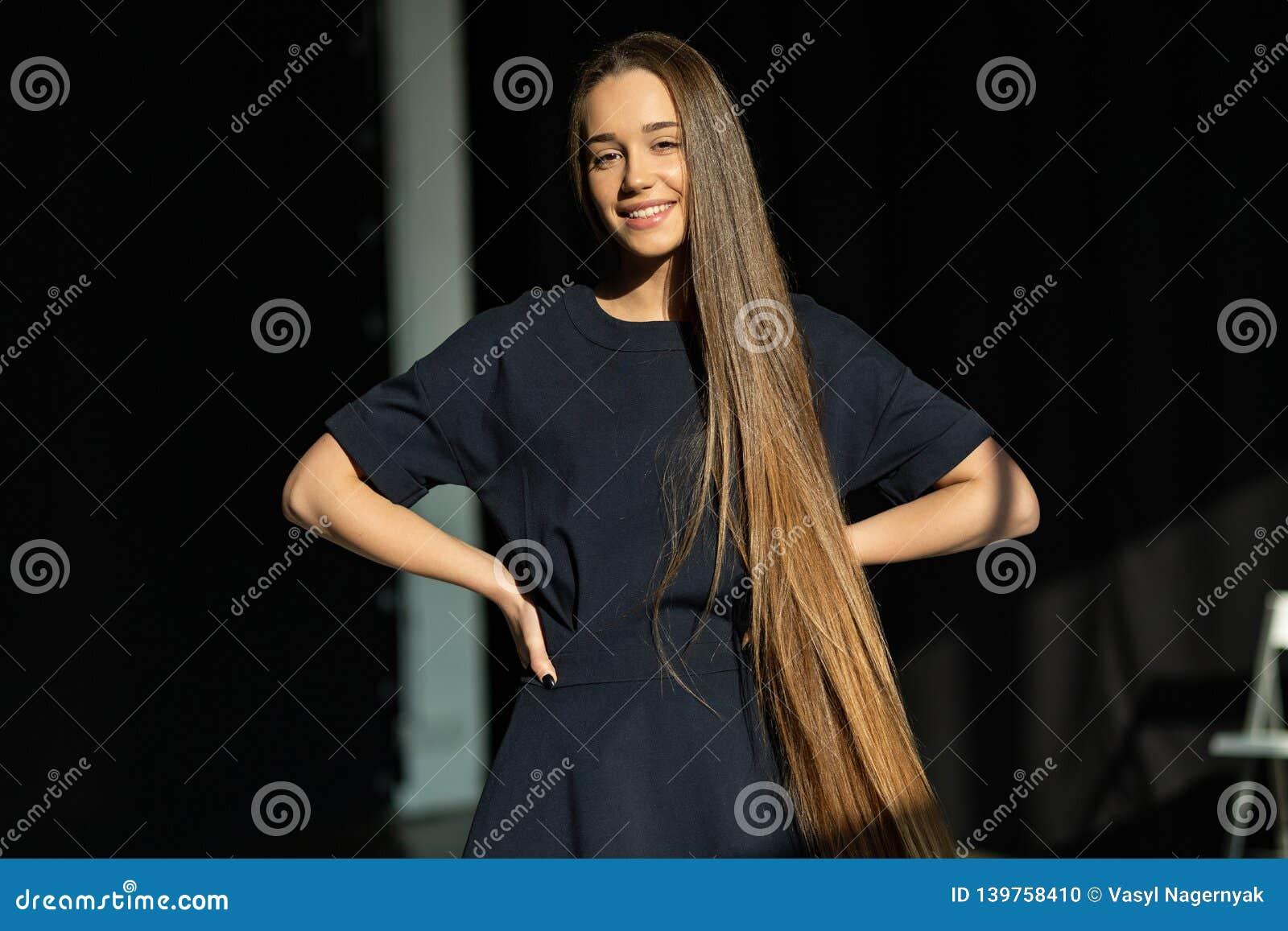 Muchacha sonriente hermosa con el pelo recto largo en vestido negro
