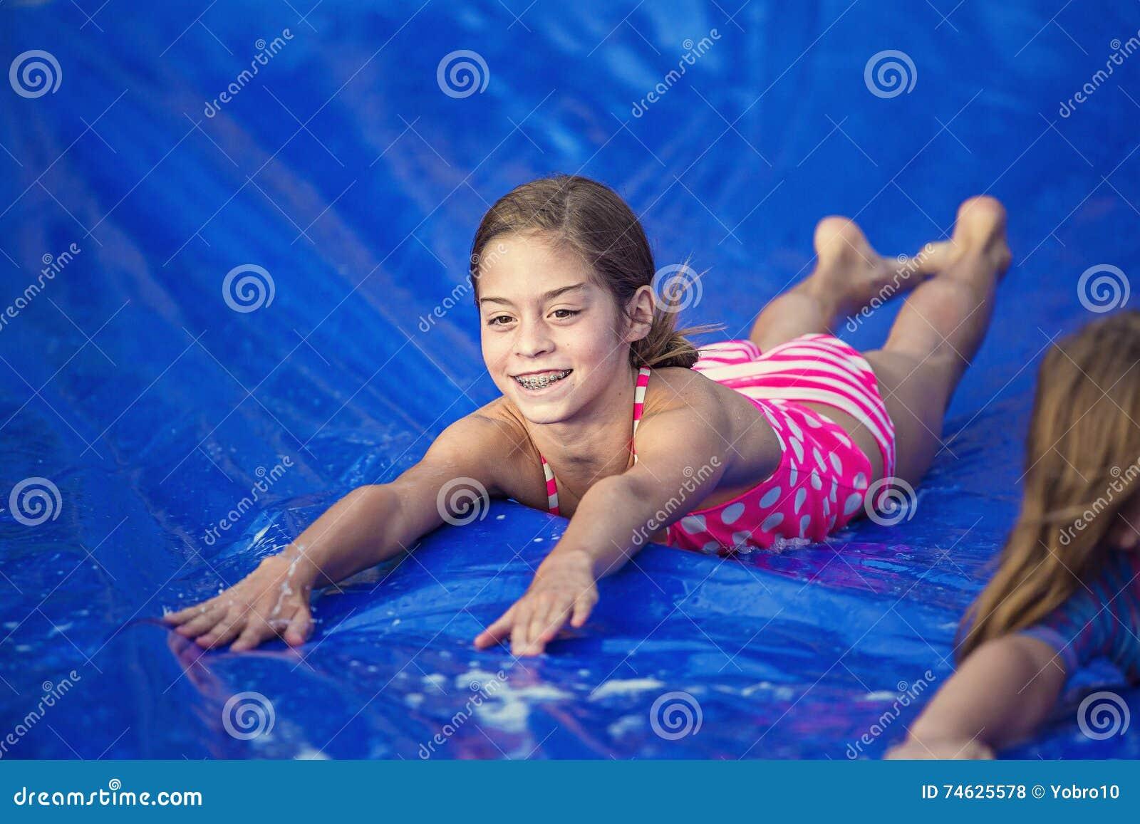 Muchacha sonriente que desliza abajo un resbalón y una diapositiva al aire libre