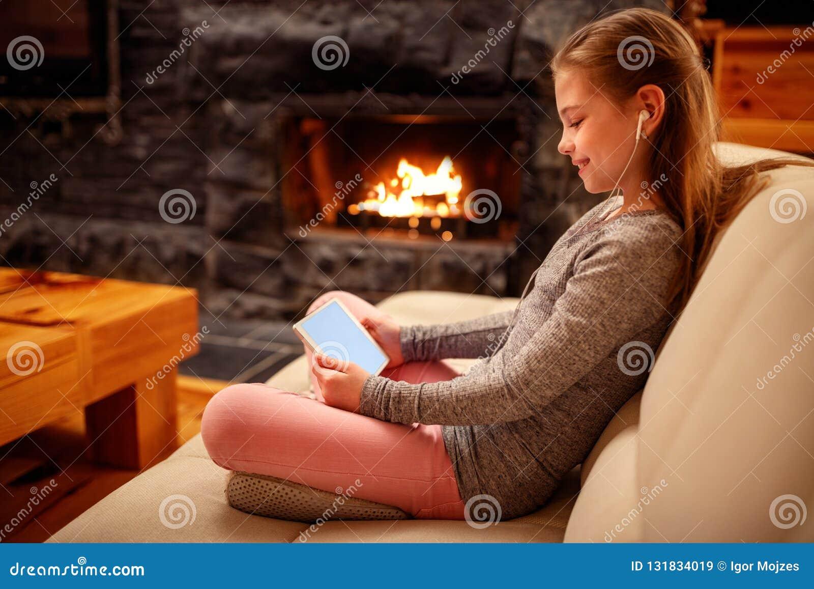 Muchacha sonriente que usa la tableta de la calculadora numérica del iPad en la cama para el educa