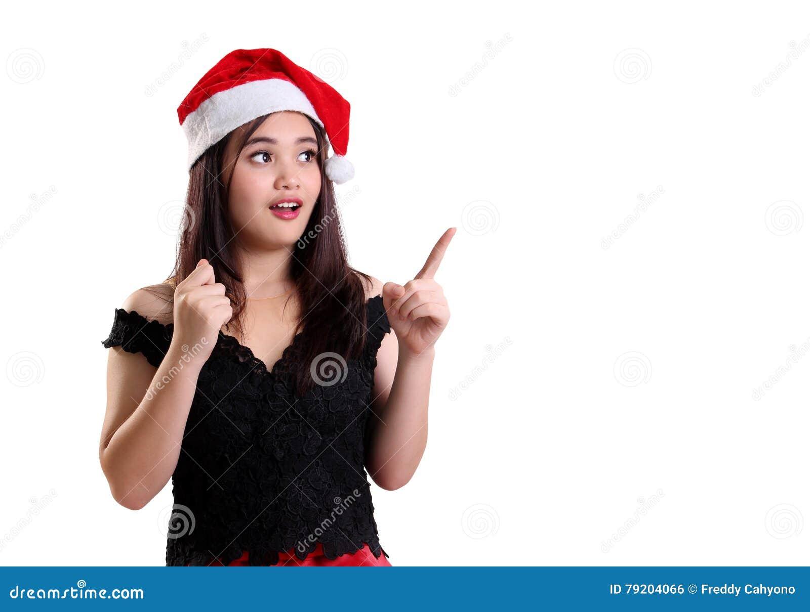 Muchacha sorprendida de la Navidad que señala en el copyspace