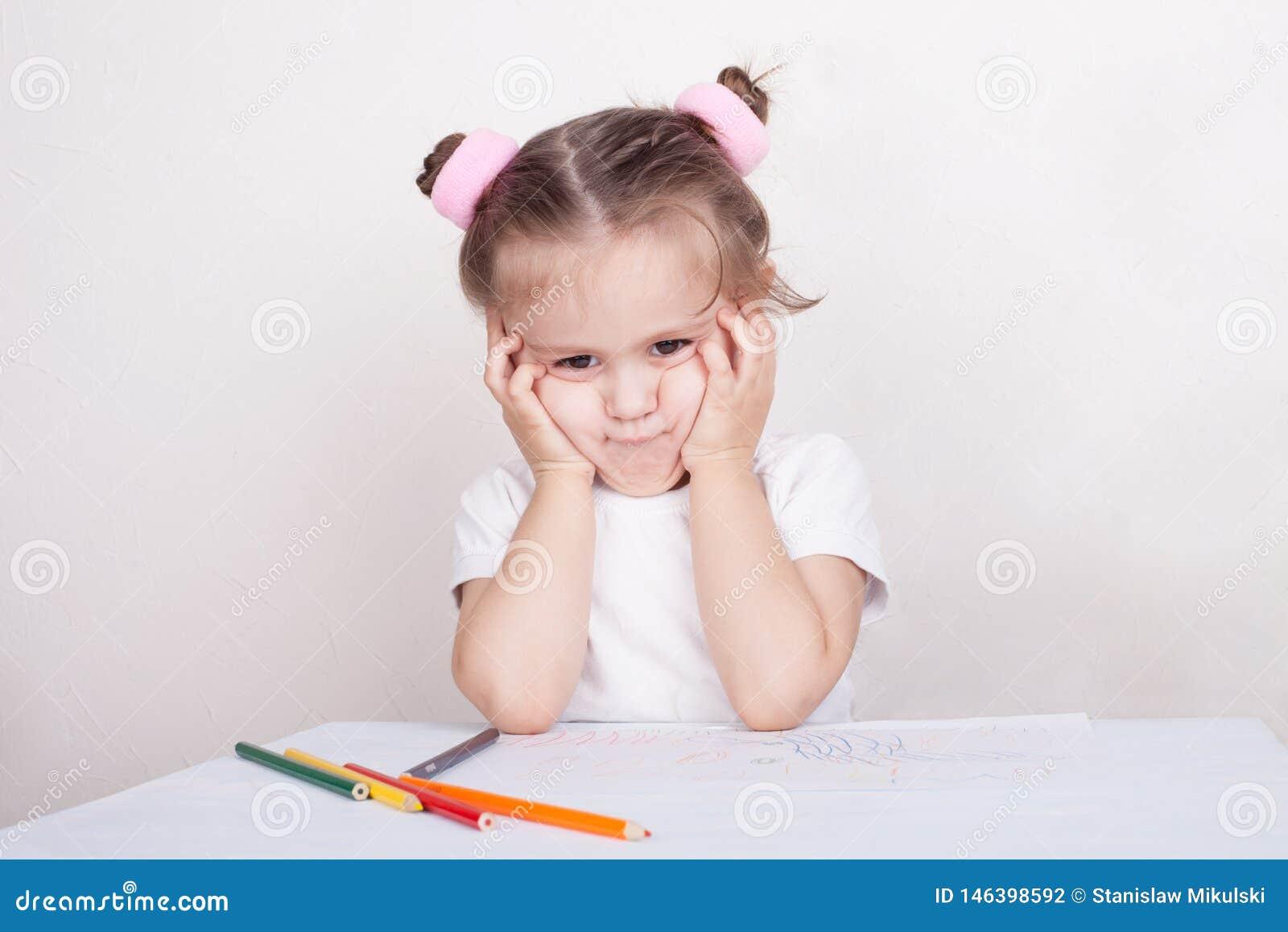 Muchacha triste con los lápices coloreados