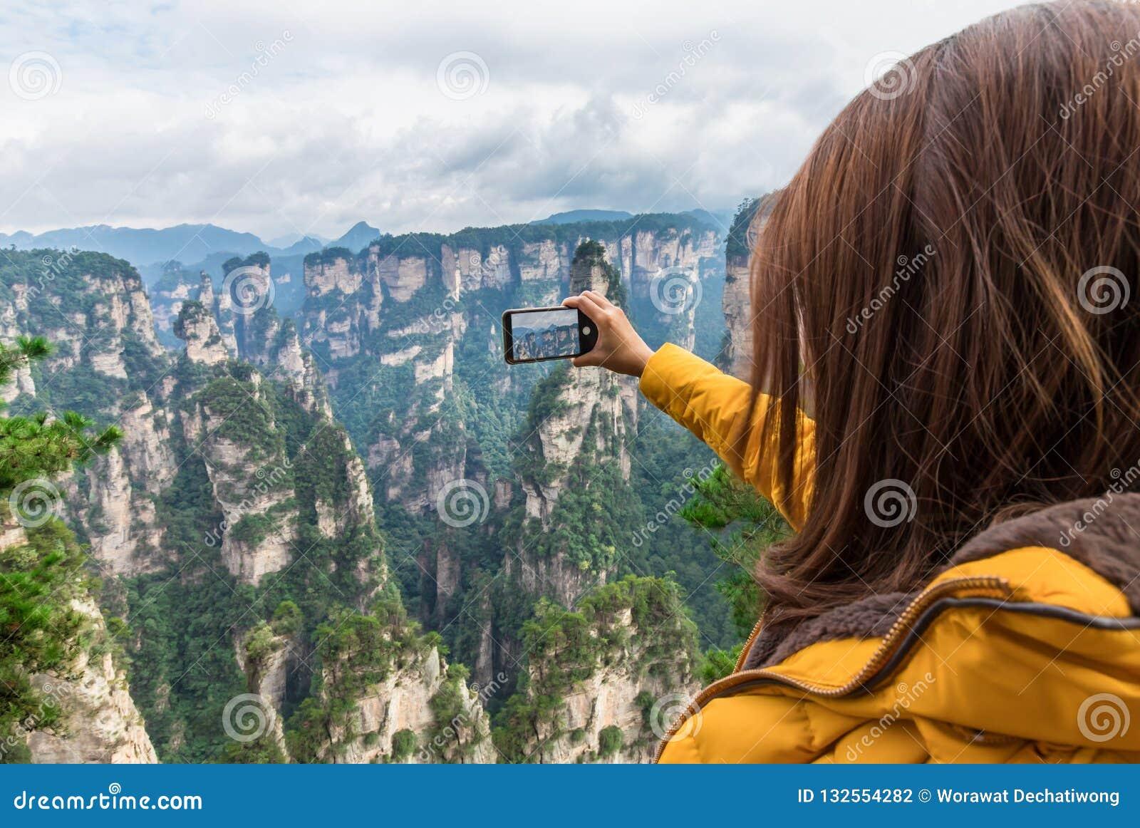 Muchacha turística asiática que toma una foto usando un teléfono elegante en Zhangji