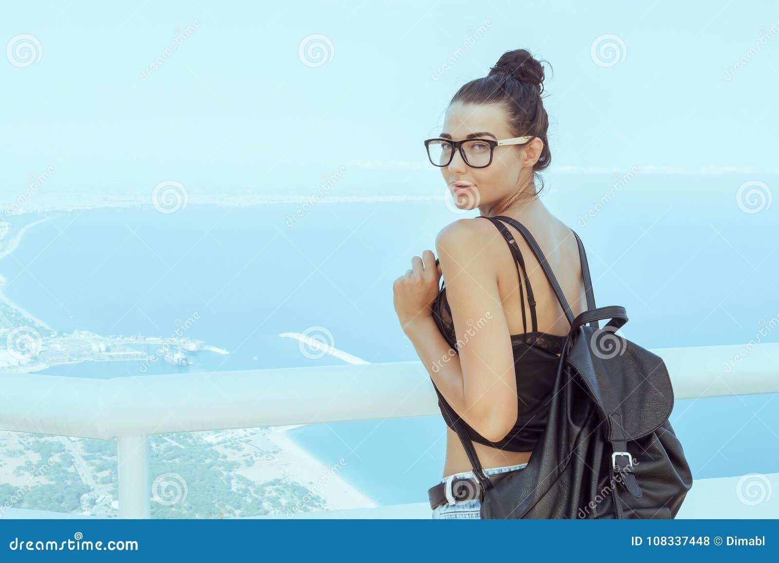 Muchacha turística joven hermosa con la mochila cerca del mar