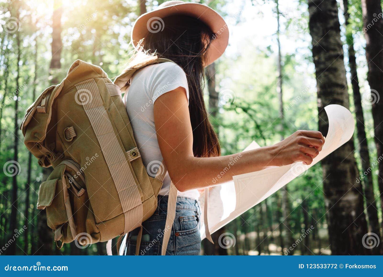 Muchacha valiente del inconformista que viaja solamente y que mira alrededor en bosque en mapa de ubicación de la mochila y del c