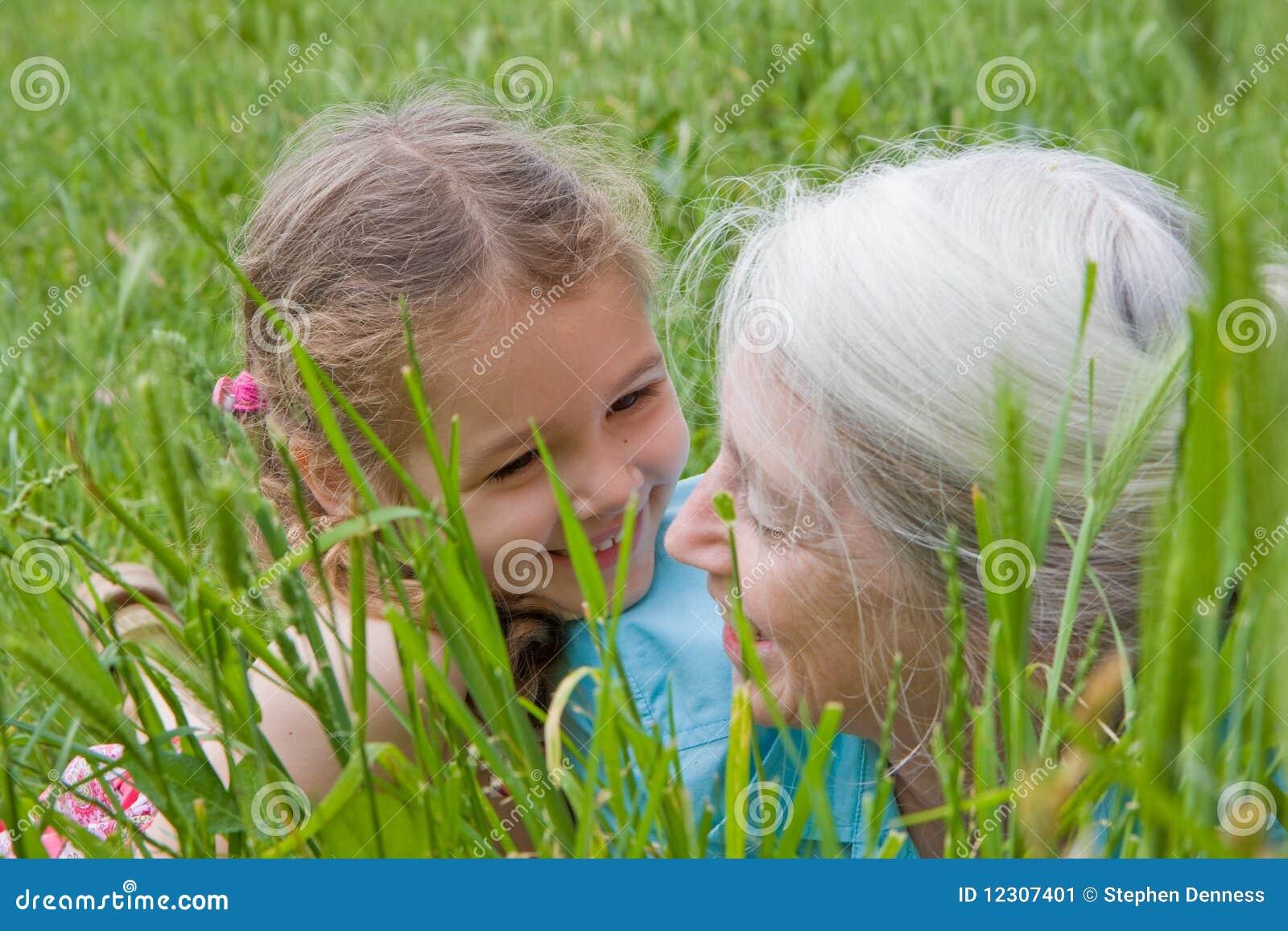 Muchacha y abuela que se divierten en hierba larga