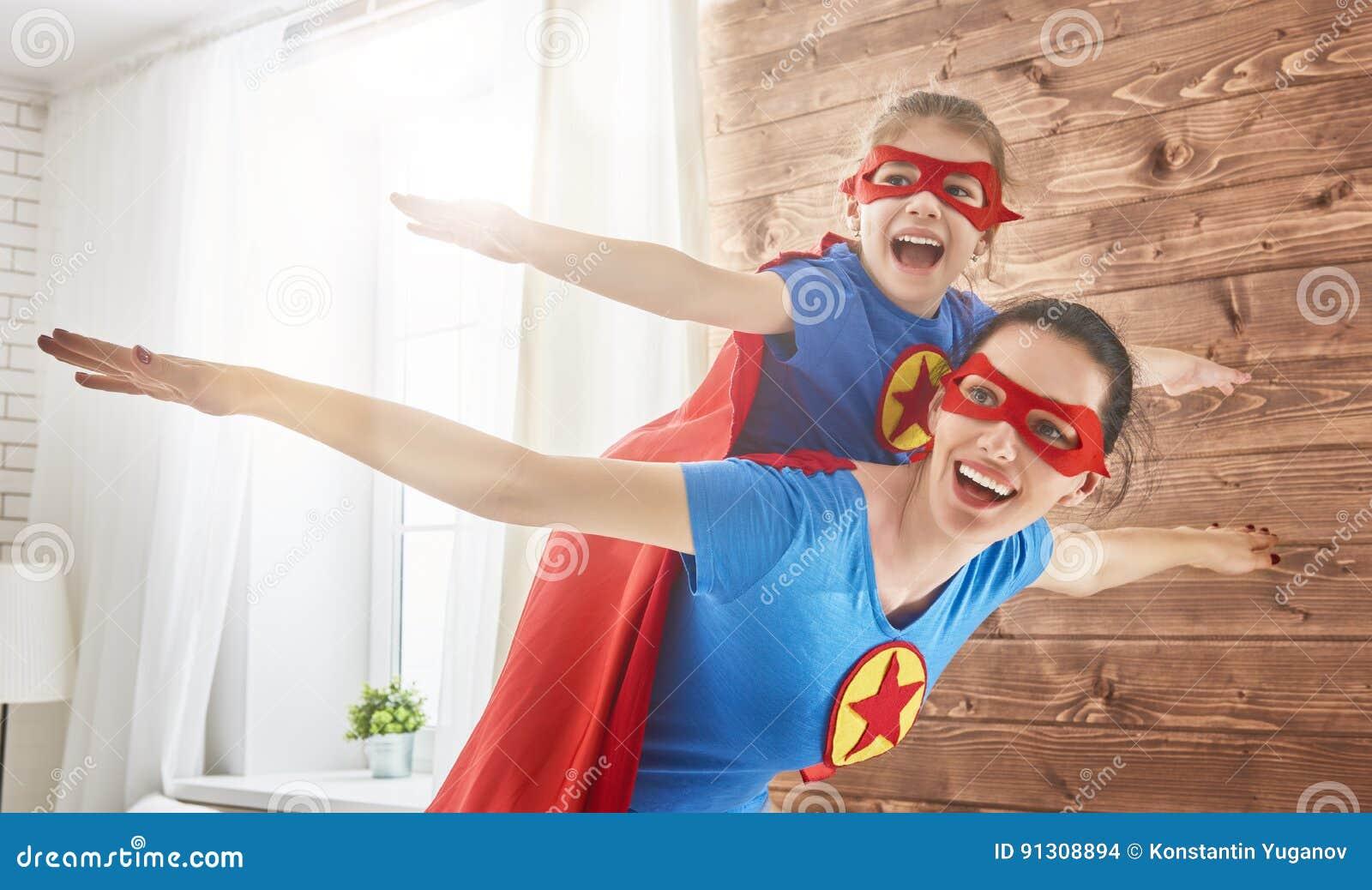 Muchacha y mamá en trajes del super héroe