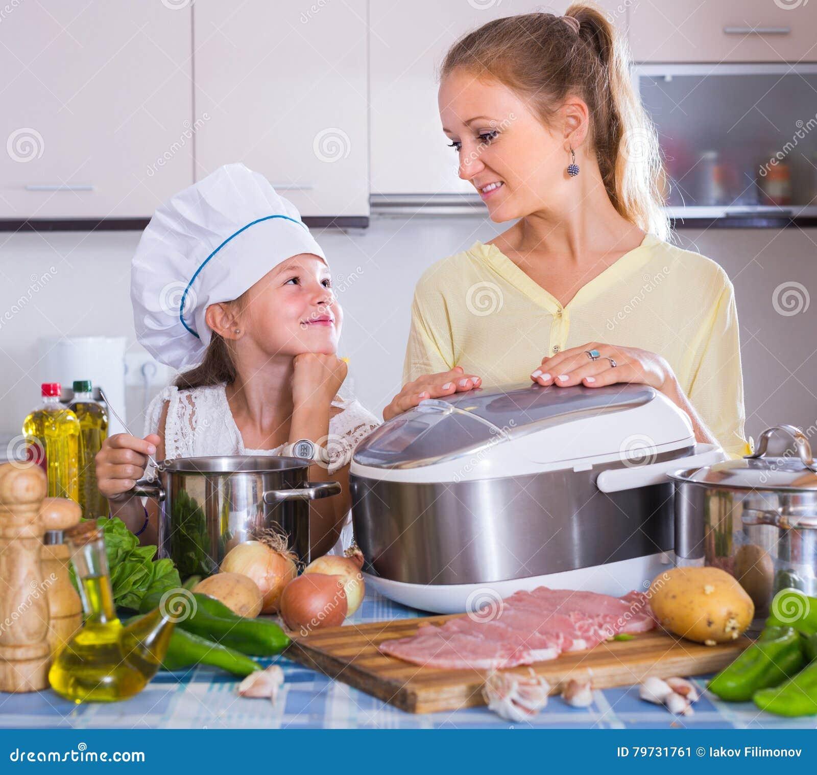Muchacha y mamá que cocinan con el multicooker