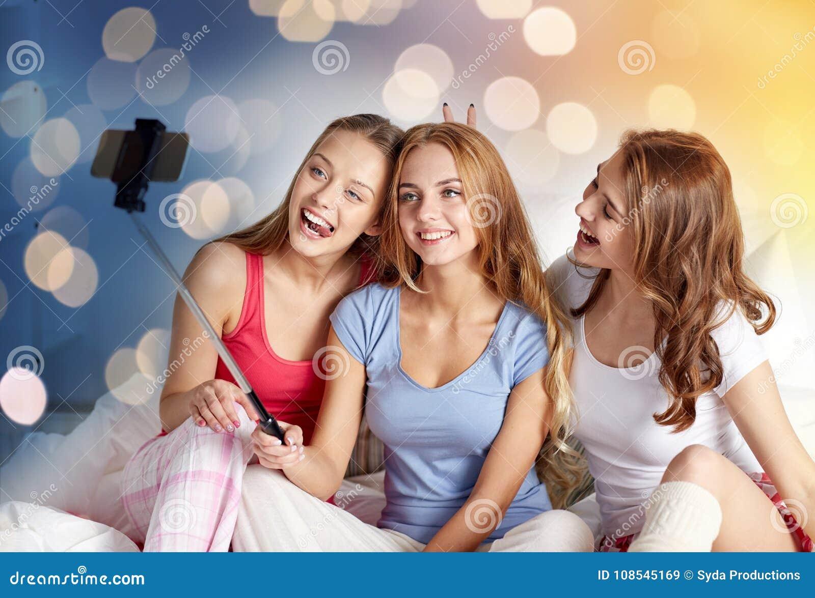 Muchachas adolescentes con el smartphone que toma el selfie en casa