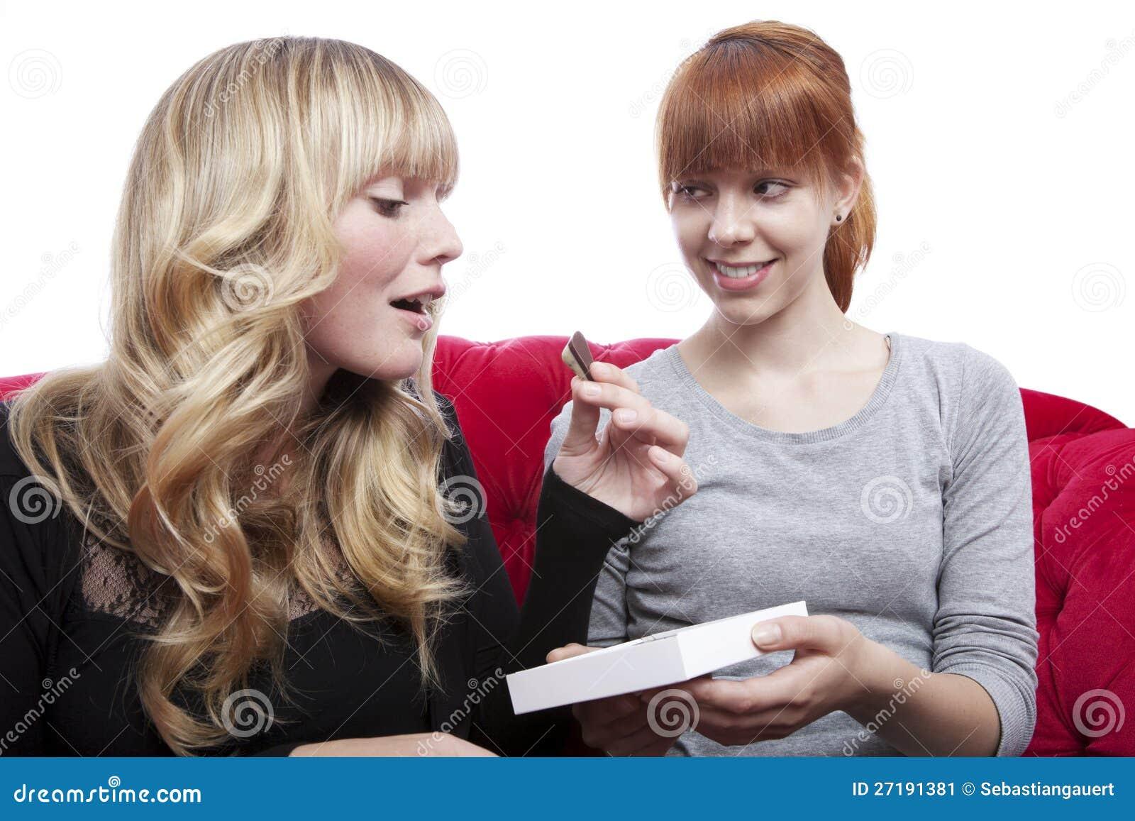Muchachas bonitas jovenes que comen el chocolate