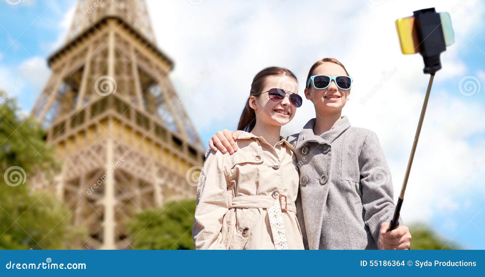 Muchachas con el palillo del selfie del smartphone en la torre Eiffel