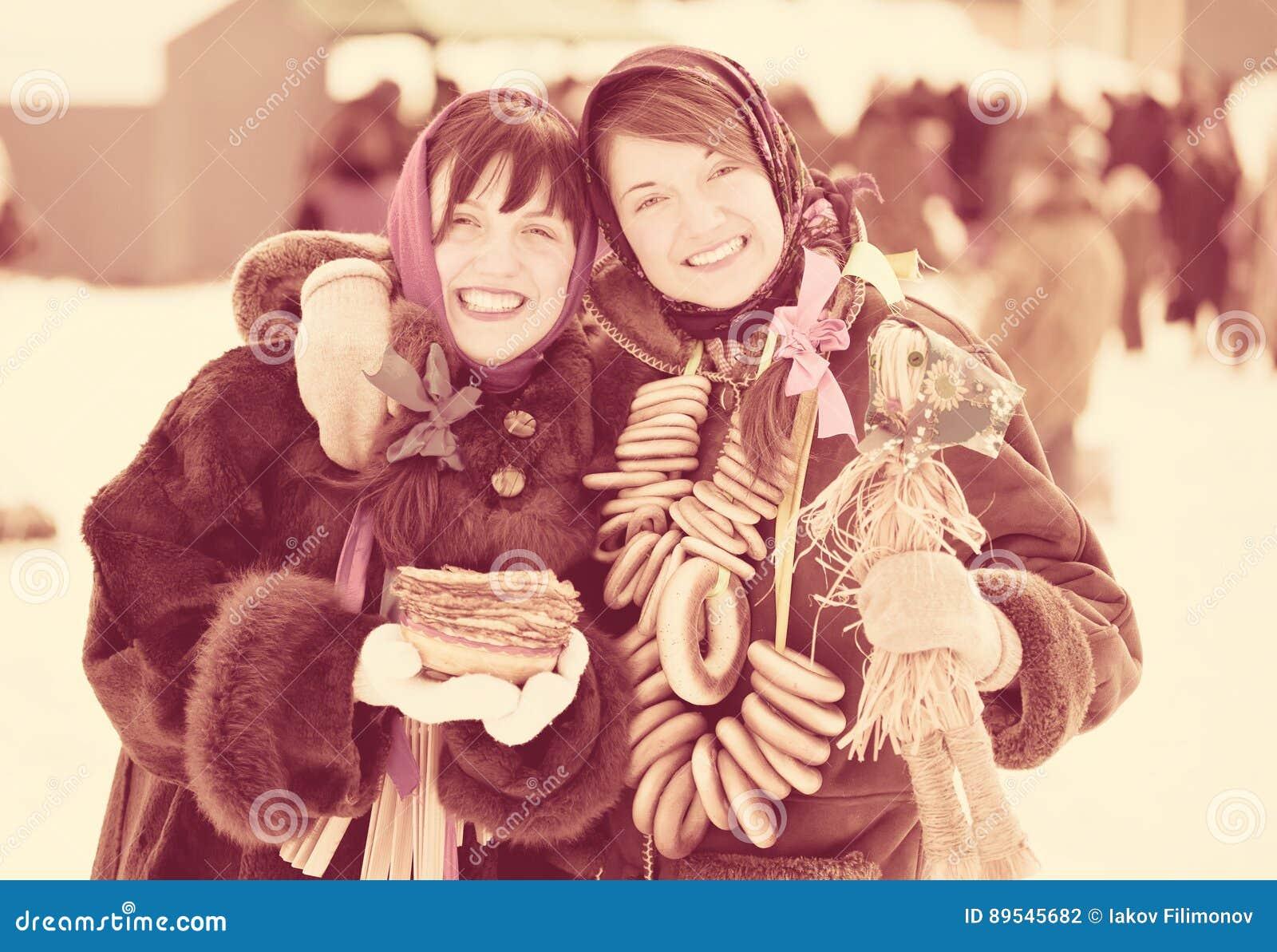 Muchachas con la crepe y la galletita crujiente redonda durante Shrovetide