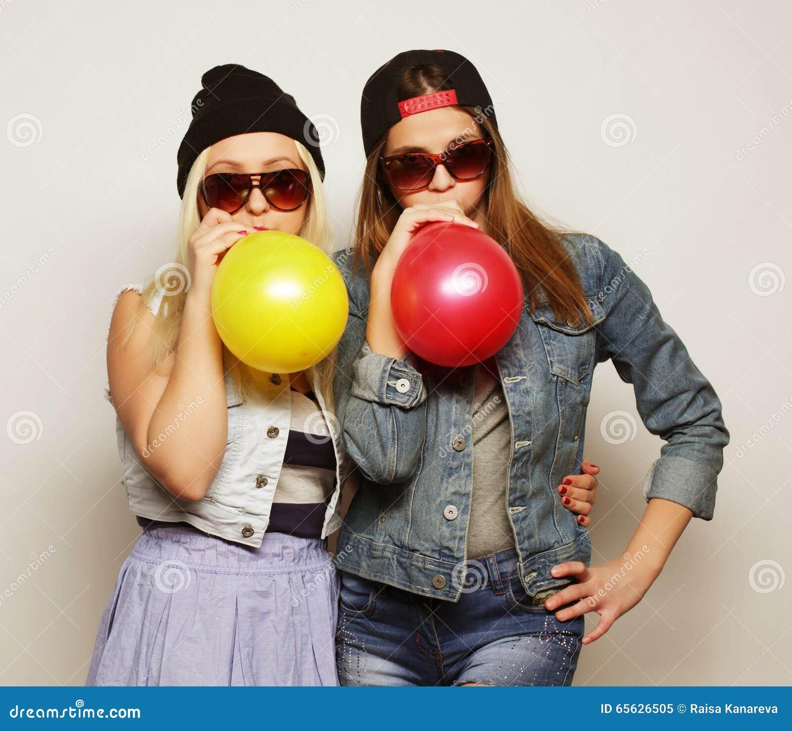 Muchachas del inconformista que sonríen y que sostienen los globos coloreados
