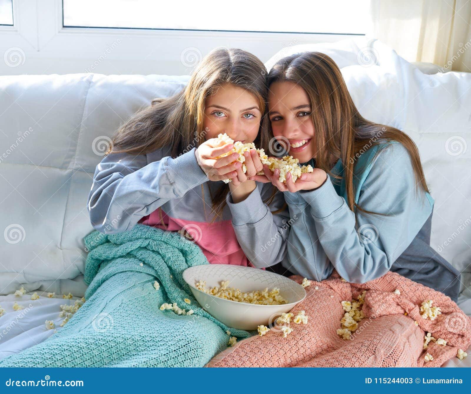 Muchachas del mejor amigo en el sofá que se divierte con palomitas