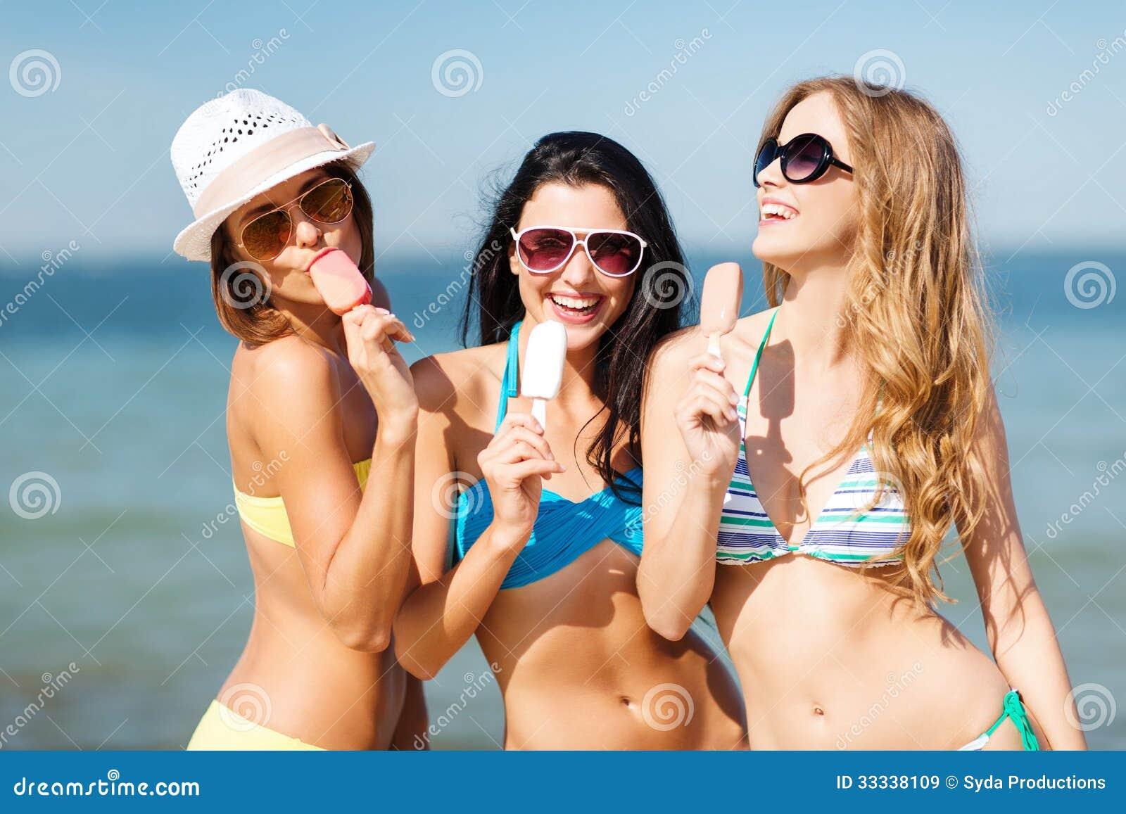 Muchachas En Bikini Con Helado En La Playa Imagen De Archivo