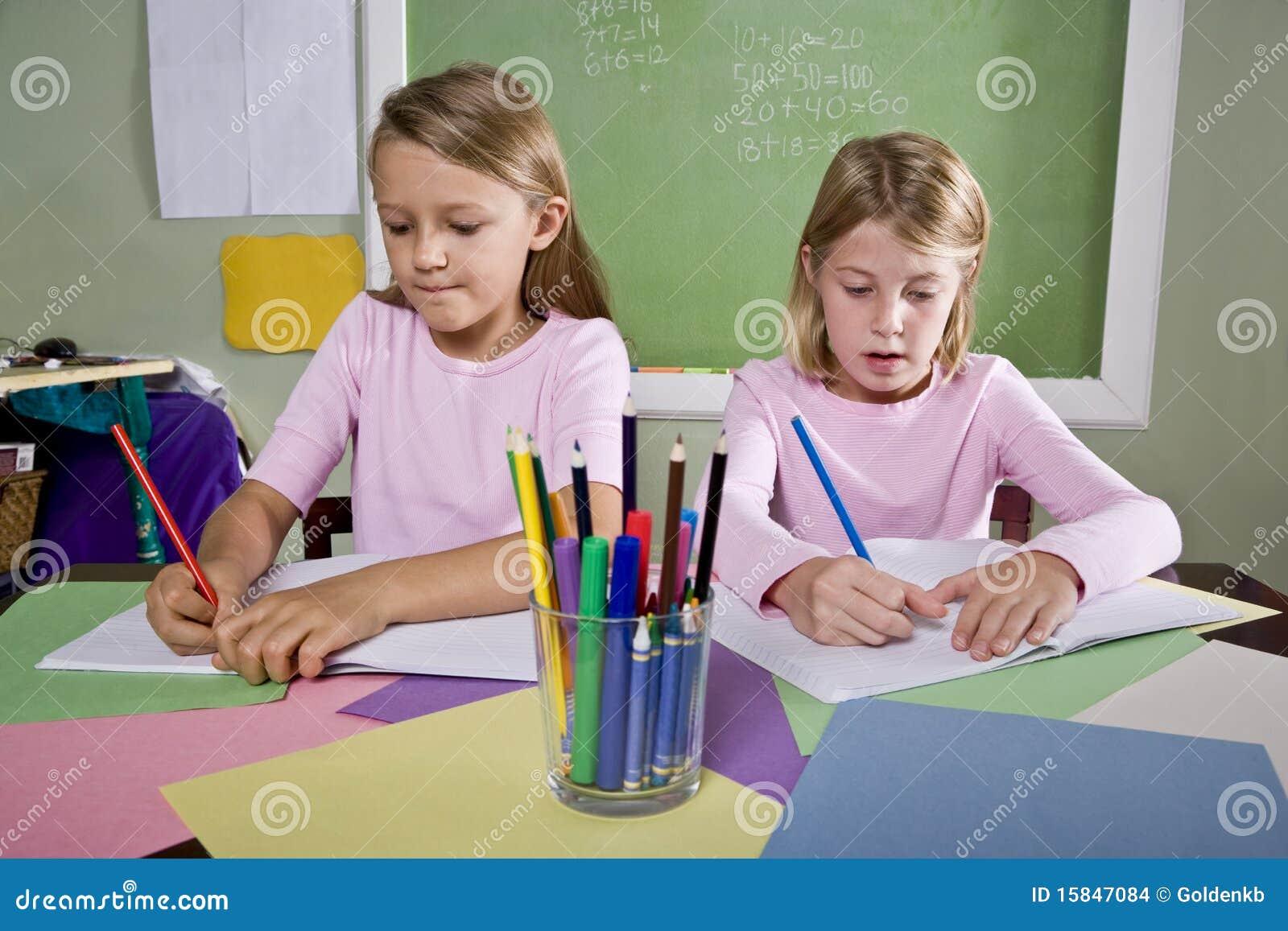 Muchachas en la sala de clase que hace el schoolwork, escribiendo