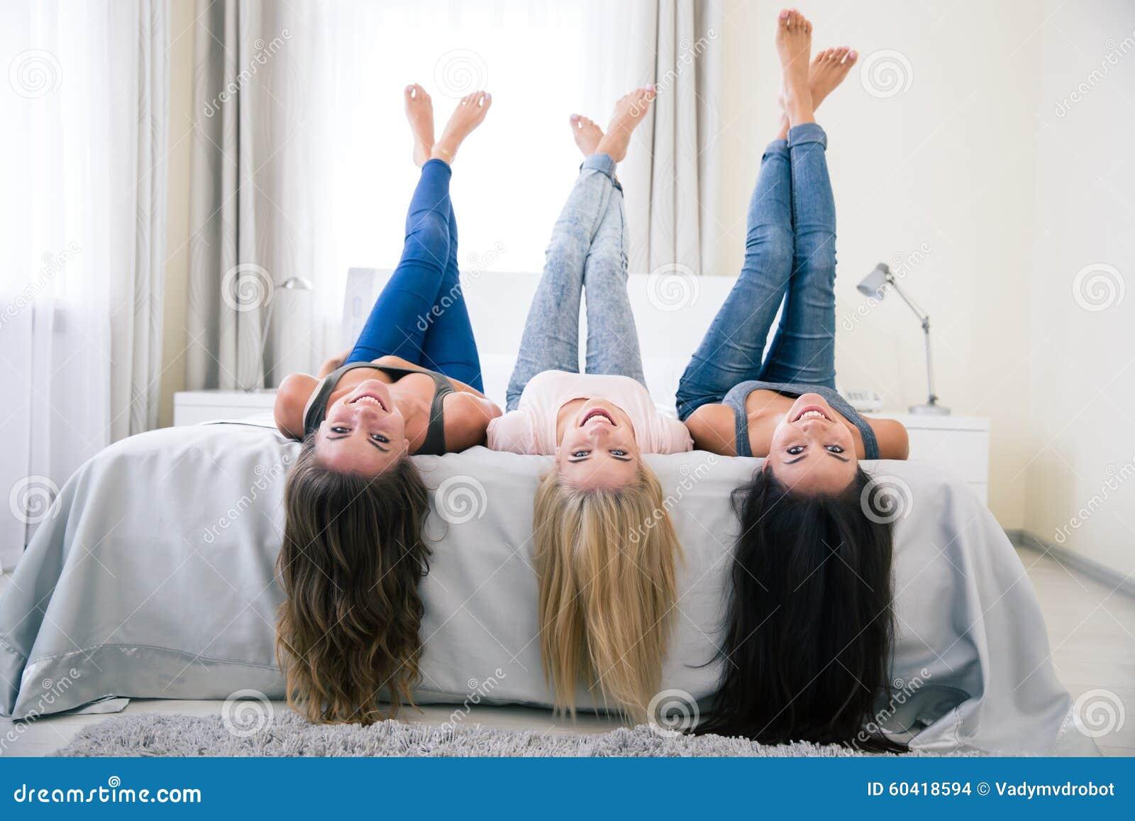 Muchachas felices que mienten en la cama con las piernas aumentadas
