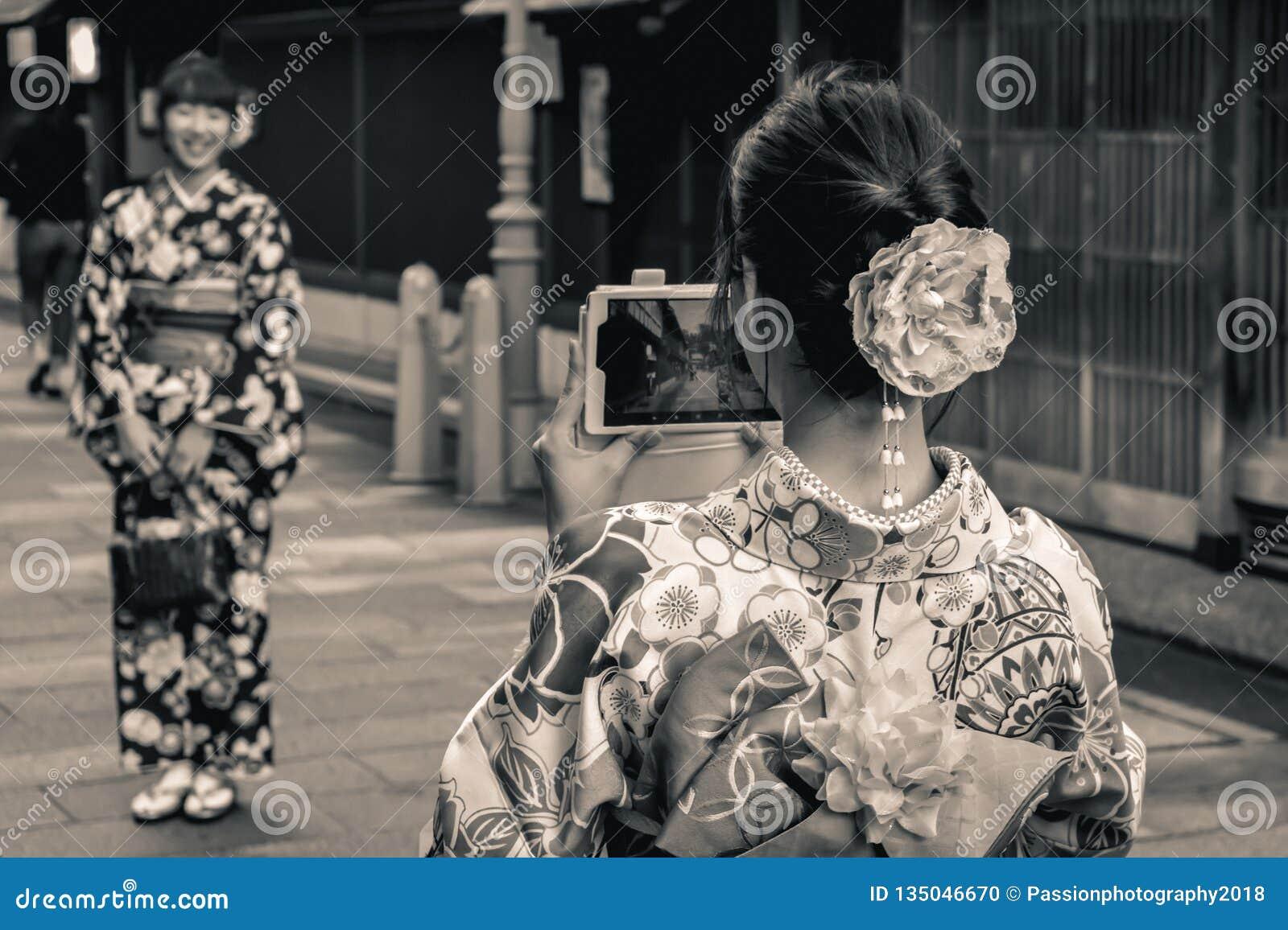 Muchachas japonesas en los yukatas tradicionales del verano que toman las fotos de uno a con el teléfono móvil pasado de la tecno
