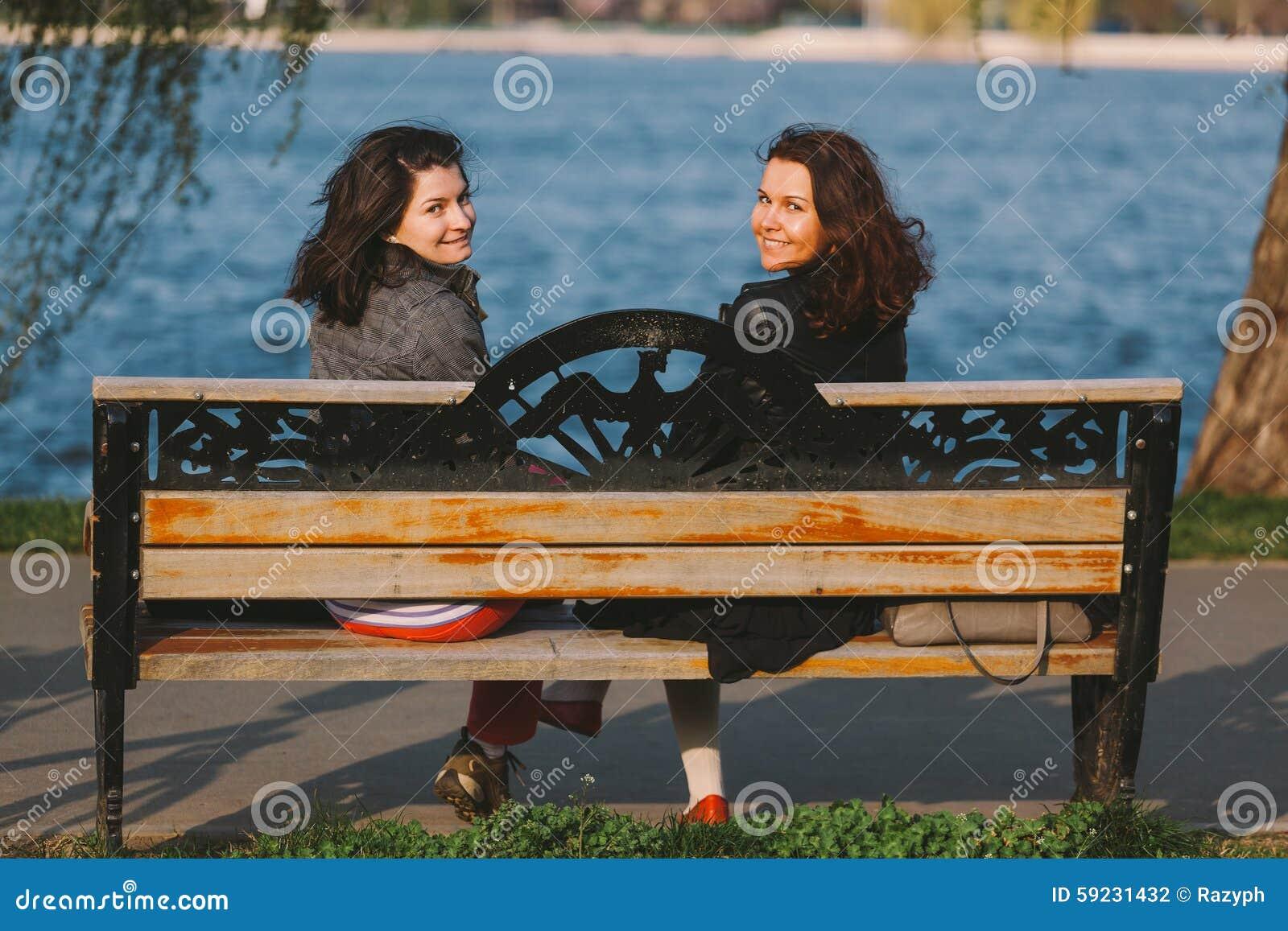 Muchachas lindas que se sientan en un banco de madera, sonriendo