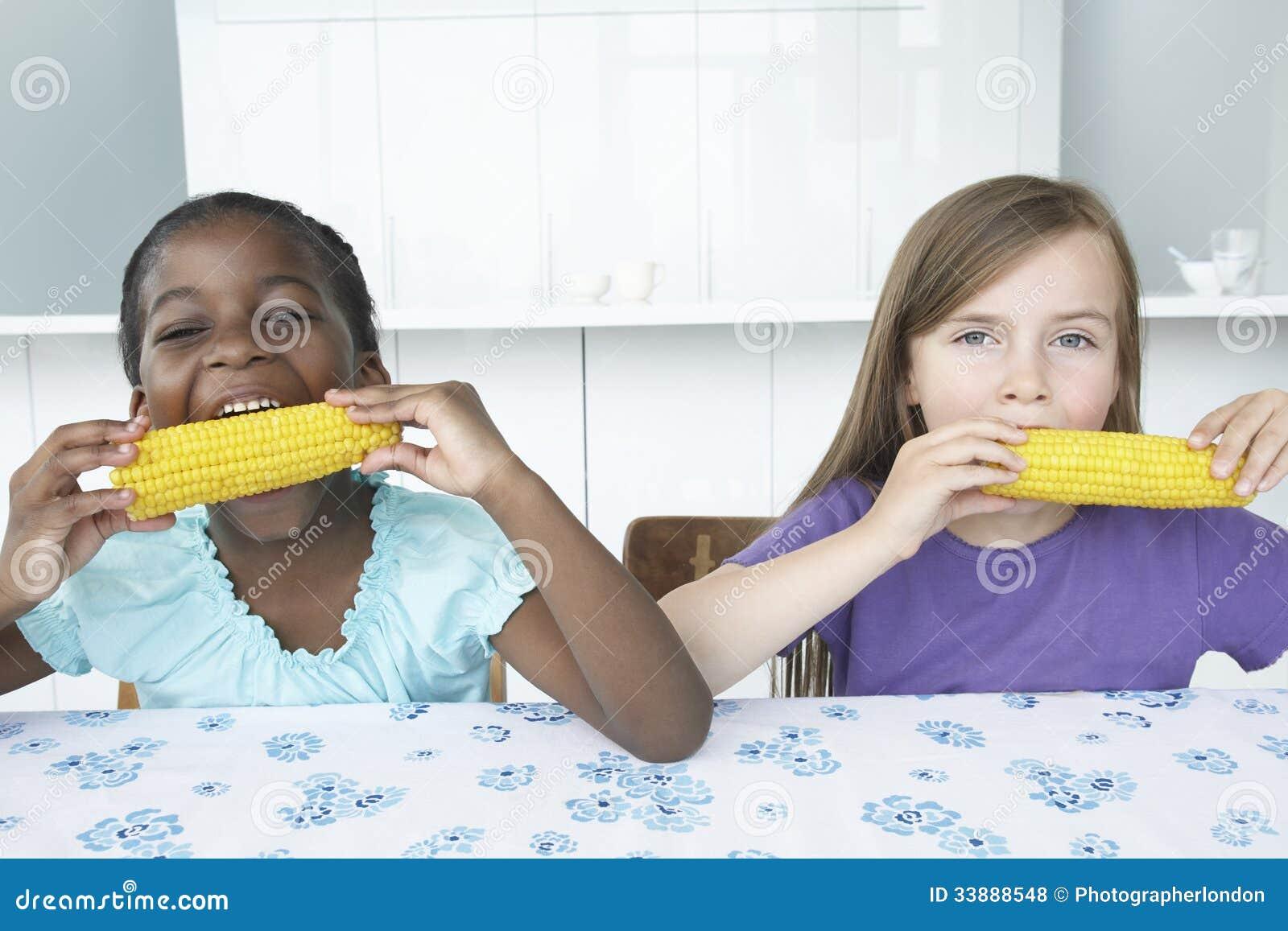 Muchachas multiétnicas que comen mazorcas de maíz