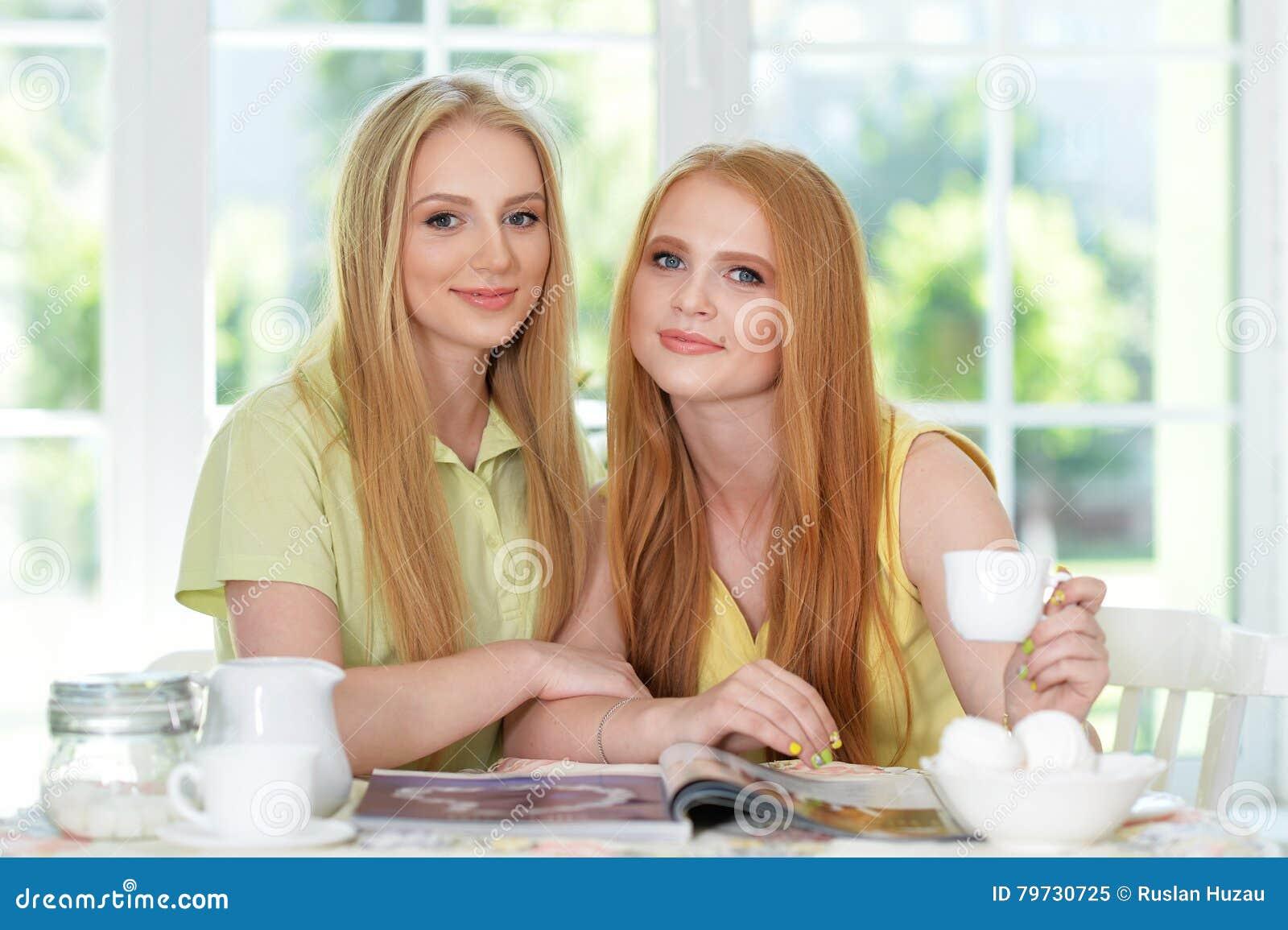 Muchachas que beben té con la revista