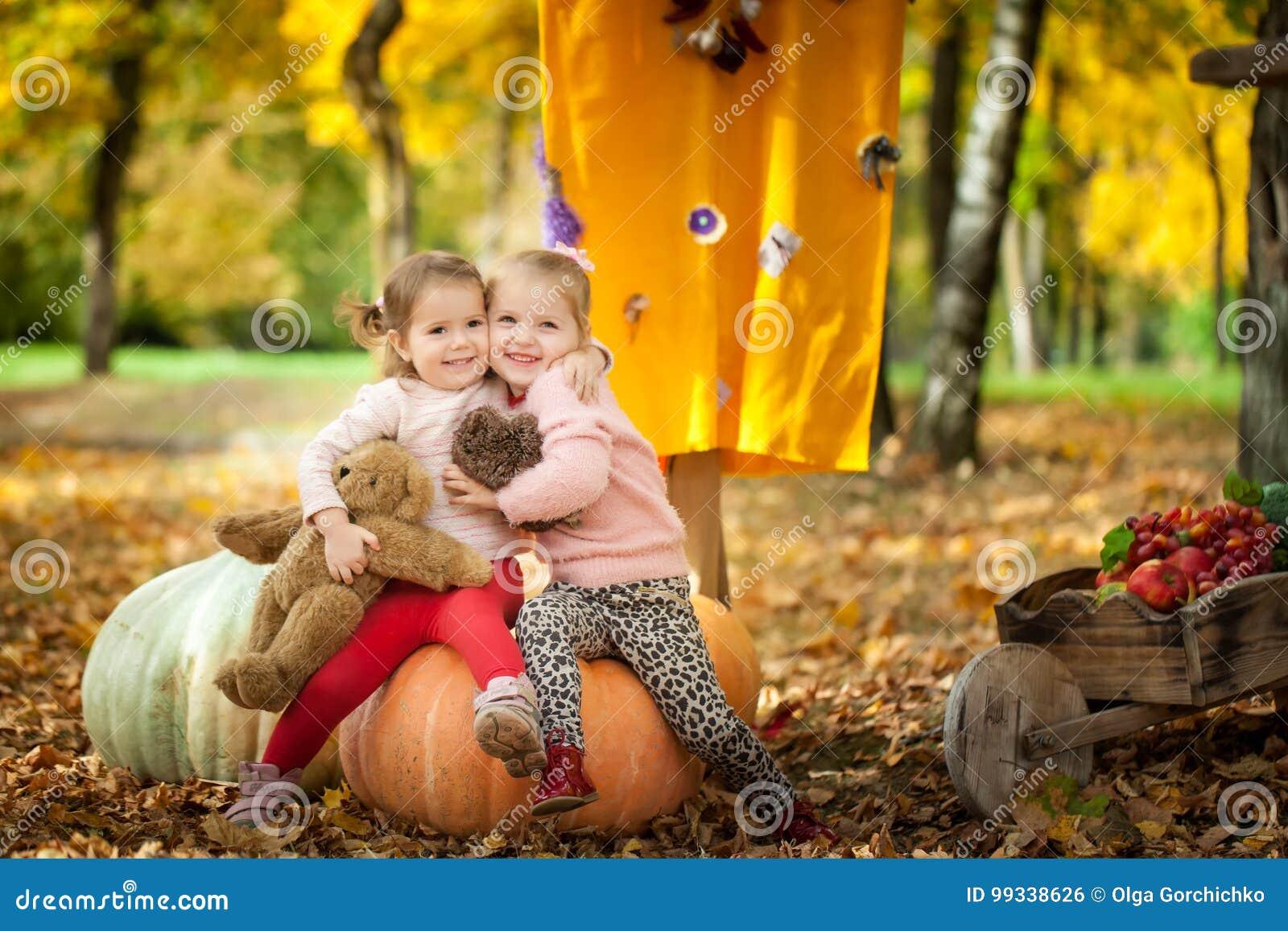 Muchachas sonrientes en el parque del otoño