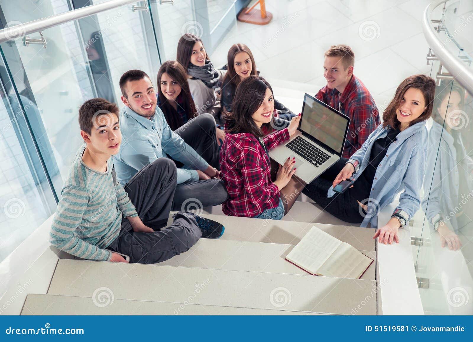 Muchachas y muchachos adolescentes felices en las escaleras escuela o universidad