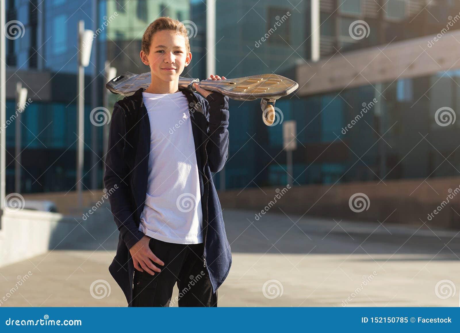 Muchacho adolescente lindo con el monopatín al aire libre, colocándose en la calle